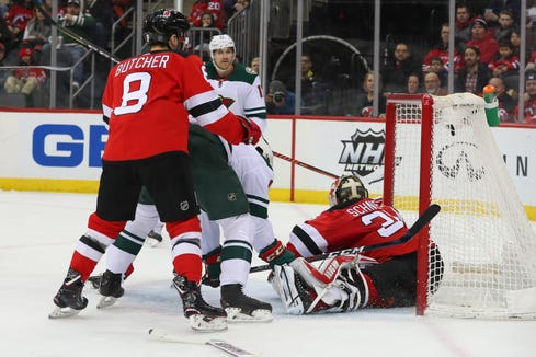 Feb 9, 2019; Newark, NJ, USA; Minnesota Wild left wing Marcus Foligno (17) scores a goal against New Jersey Devils goaltender Cory Schneider (35) during the first period at Prudential Center.