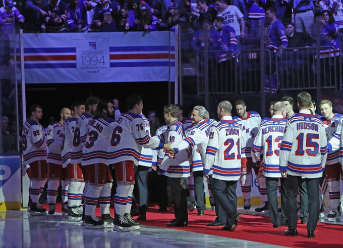 NEW YORK, NEW YORK - FEBRUARY 08: The current New York Rangers team shakes hands with the Rangers Stanley Cup winning team of 1994 following a ceremony prior to the Rangers game against the Carolina Hurricanes at Madison Square Garden on February 08, 2019 in New York City. The Rangers were celebrating the 25th anniversary of their Stanley Cup win in 1994.
