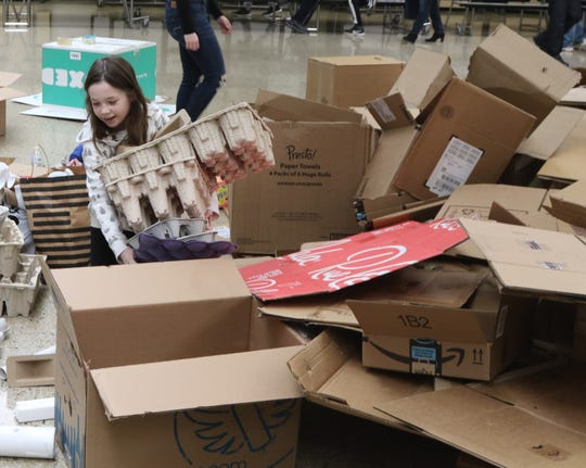 Kiera Stankard 9 carries some samples of cardboard from the supply pile, to use for her upcoming project as she competes in the Cardboard Animal-a-thon at Ramapo HS where she was helped by high school engineering students who worked on and displayed projects, making mechanical animals out of cardboard. They also helped younger students work on projects during the event held at Ramapo HS on February 9, 2019.