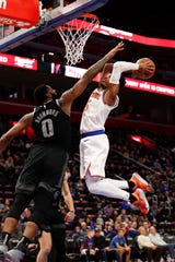 Feb 8, 2019; Detroit, MI, USA; New York Knicks guard Dennis Smith Jr. (5) attempts a dunk against Detroit Pistons center Andre Drummond (0) during the first quarter at Little Caesars Arena.