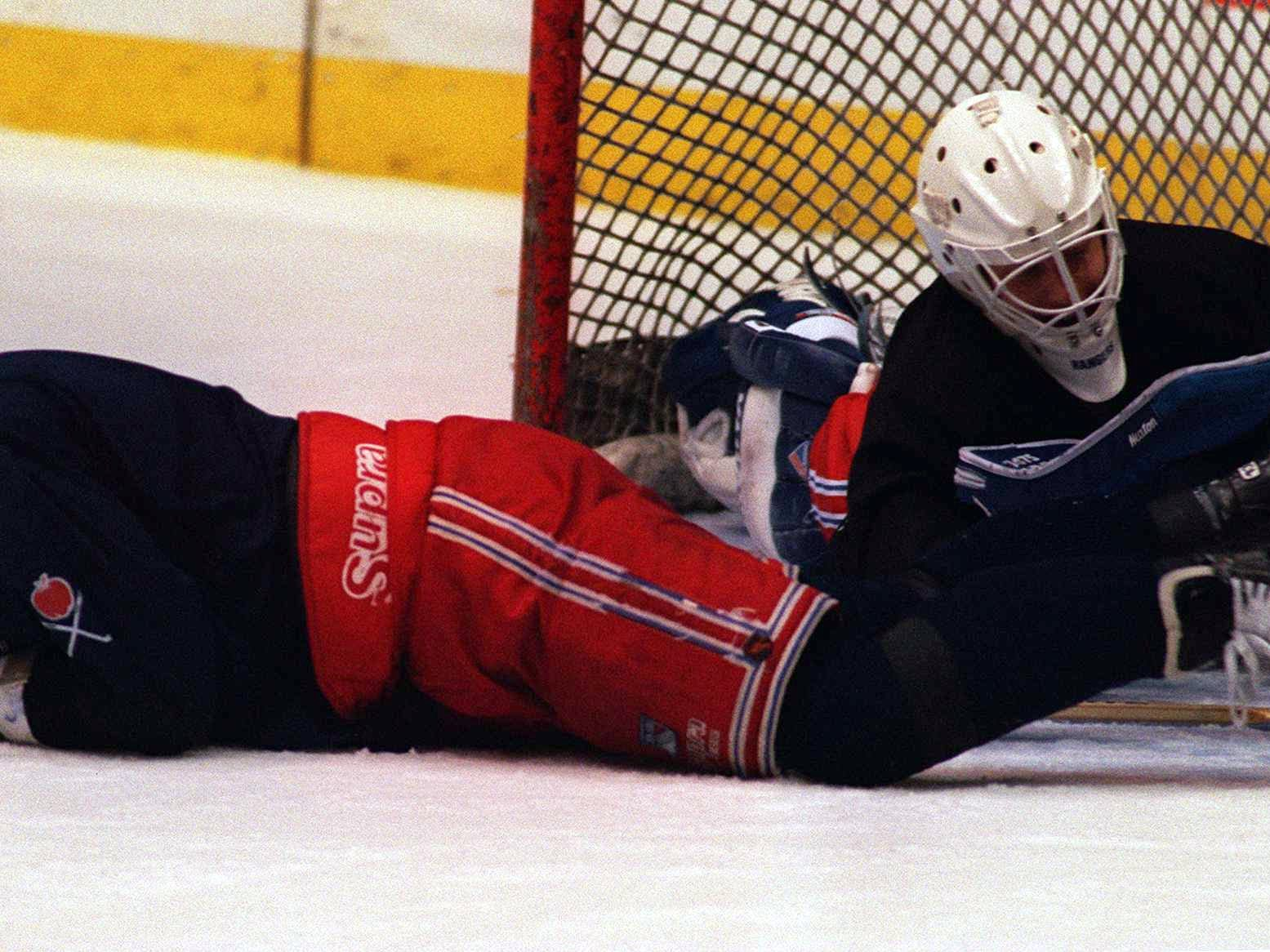 6 Jun 1994: RANGERS FORWARD ALEXEI KOVALEV, LEFT, RECOVERS FROM A LIGHT COLLISION WITH GOALTENDER COREY HIRSCH DURING TEAM WORKOUTS AT THE PACIFIC COLESIUM IN VANCOUVER, BRITISH COLUMBIA. THE RANGERS TAKE THEIR 2-1 SERIES LEAD OVER THE CANUCKS INTO GAME F