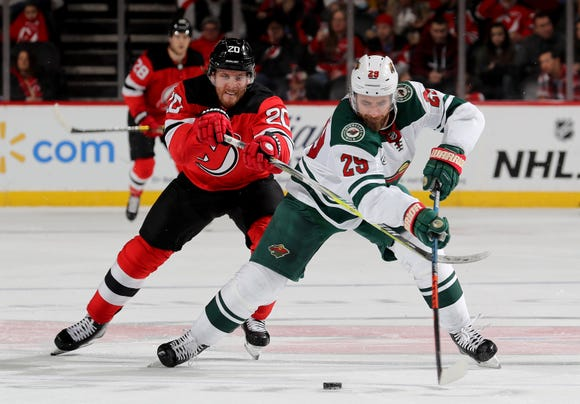NEWARK, NEW JERSEY - FEBRUARY 09:  Greg Pateryn (29) of the Minnesota Wild and Blake Coleman (20) of the New Jersey Devils try to take control of the puck at Prudential Center on February 9, 2019 in Newark, New Jersey.