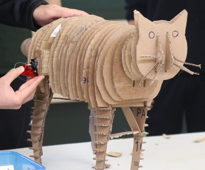 This cat made from cardboard has a motorized tail that wags as part of the Cardboard Animal-a-thon at Ramapo HS where engineering students work on and display their projects, making mechanical animals out of cardboard. They also helped younger students work on projects during the event held at Ramapo HS on February 9, 2019.