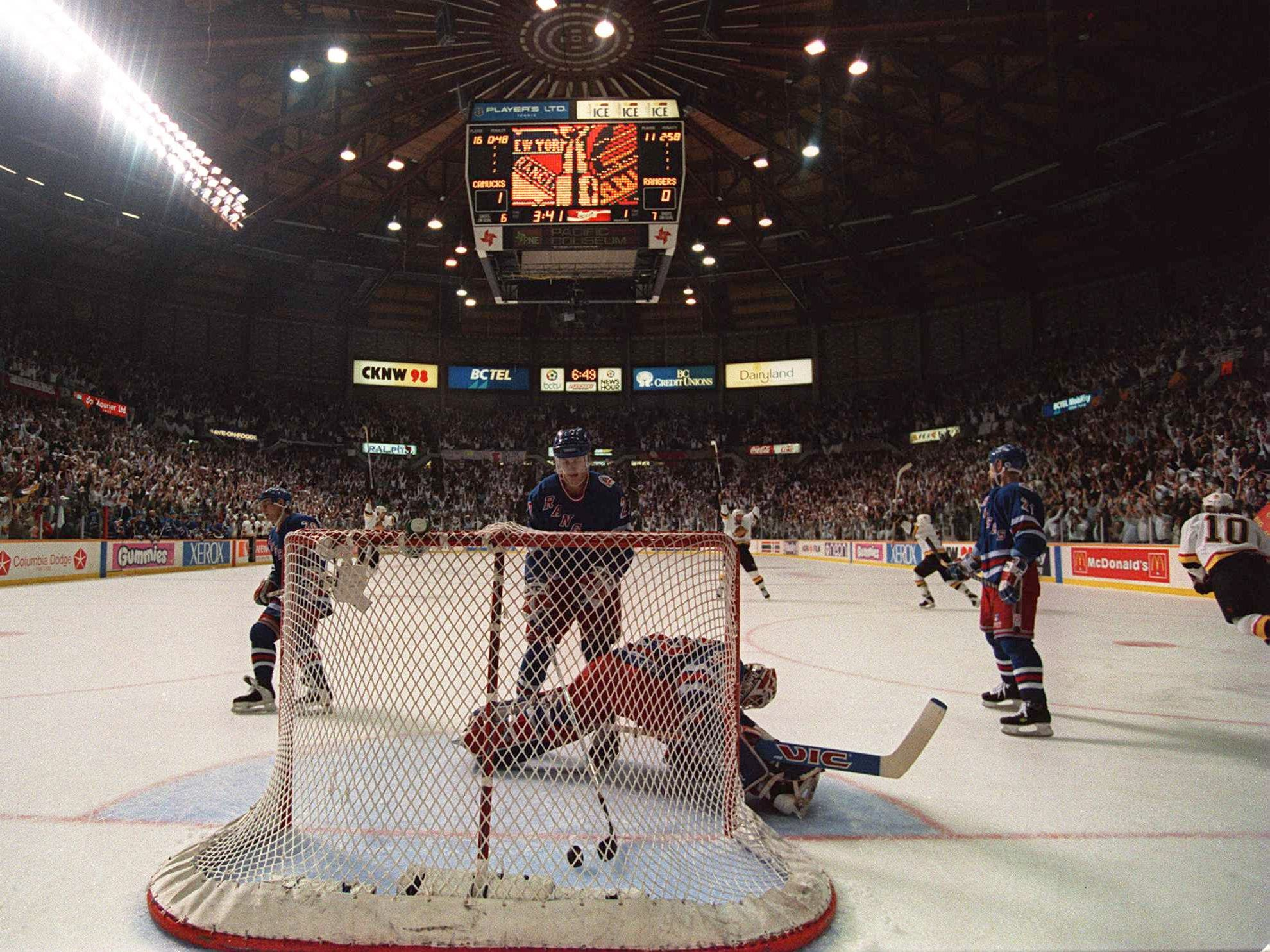 7 Jun 1994: RANGERS DEFENSEMAN BRIAN LEETCH CLEARS THE PUCK FROM THE BACK OF THE NET AS THE CANUCKS CELEBRATE AFTER CLIFF RONNING''S FIRST PERIOD GOAL TONIGHT OF GAME FOUR OF THE STANLEY CUP FINALS AT THE PACIFIC COLISEUM IN VANCOUVER, BRITISH COLUMBIA.