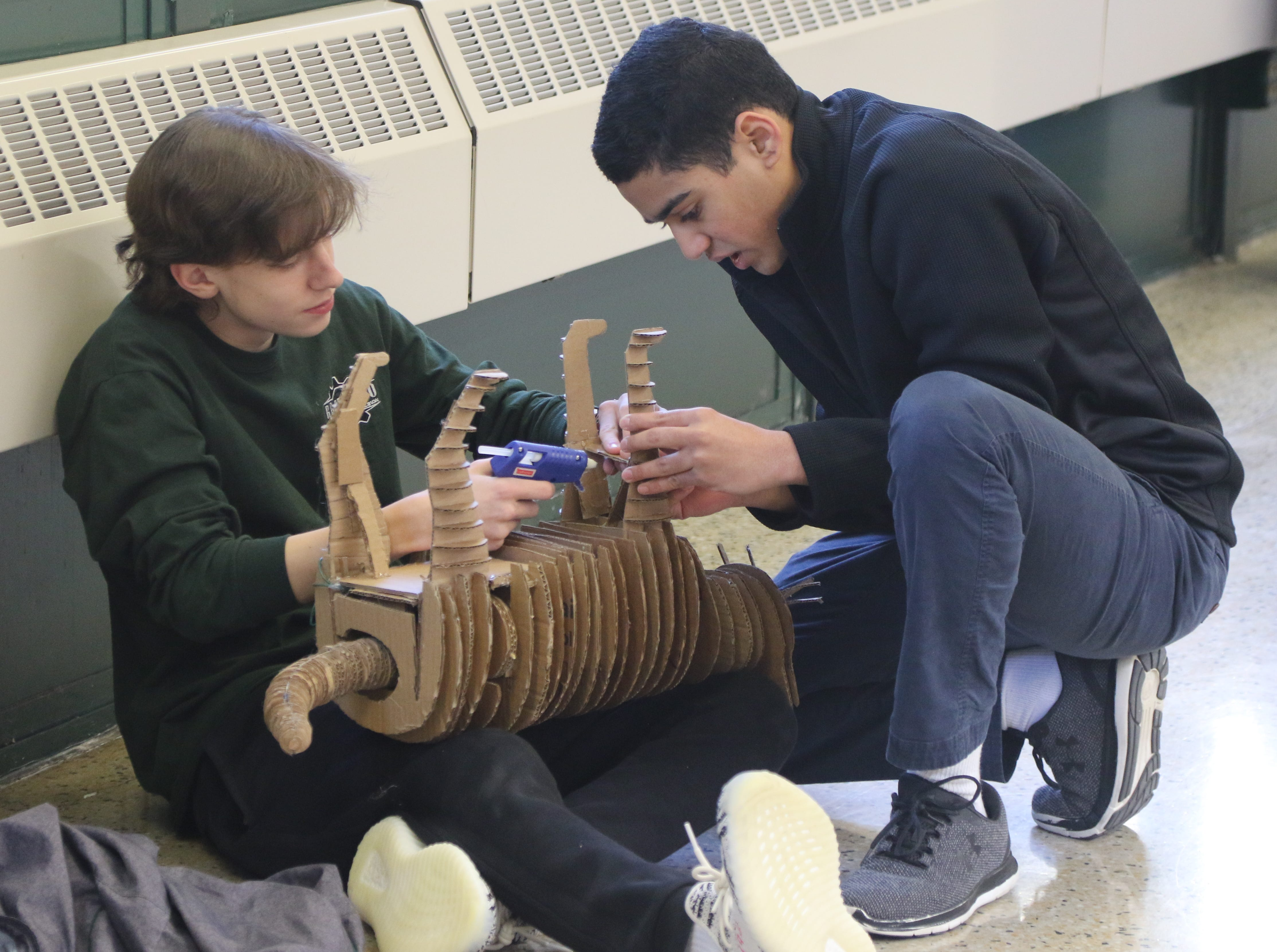 Sophomores, William Bergquist and Ian Viegas work on the final touches of Viegas' motorized tail wagging cat. This cat is made from cardboard and has a motorized tail that wags as part of the Cardboard Animal-a-thon at Ramapo HS where engineering students work on and display their projects, making mechanical animals out of cardboard. They also helped younger students work on projects during the event held at Ramapo HS on February 9, 2019.