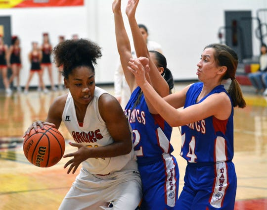 Centennial's Iysis Briggs tries to back into the lane as Las Cruces High's Alexia Gonzalez (12) and Christina Aguayo (14) put on the pressure.
