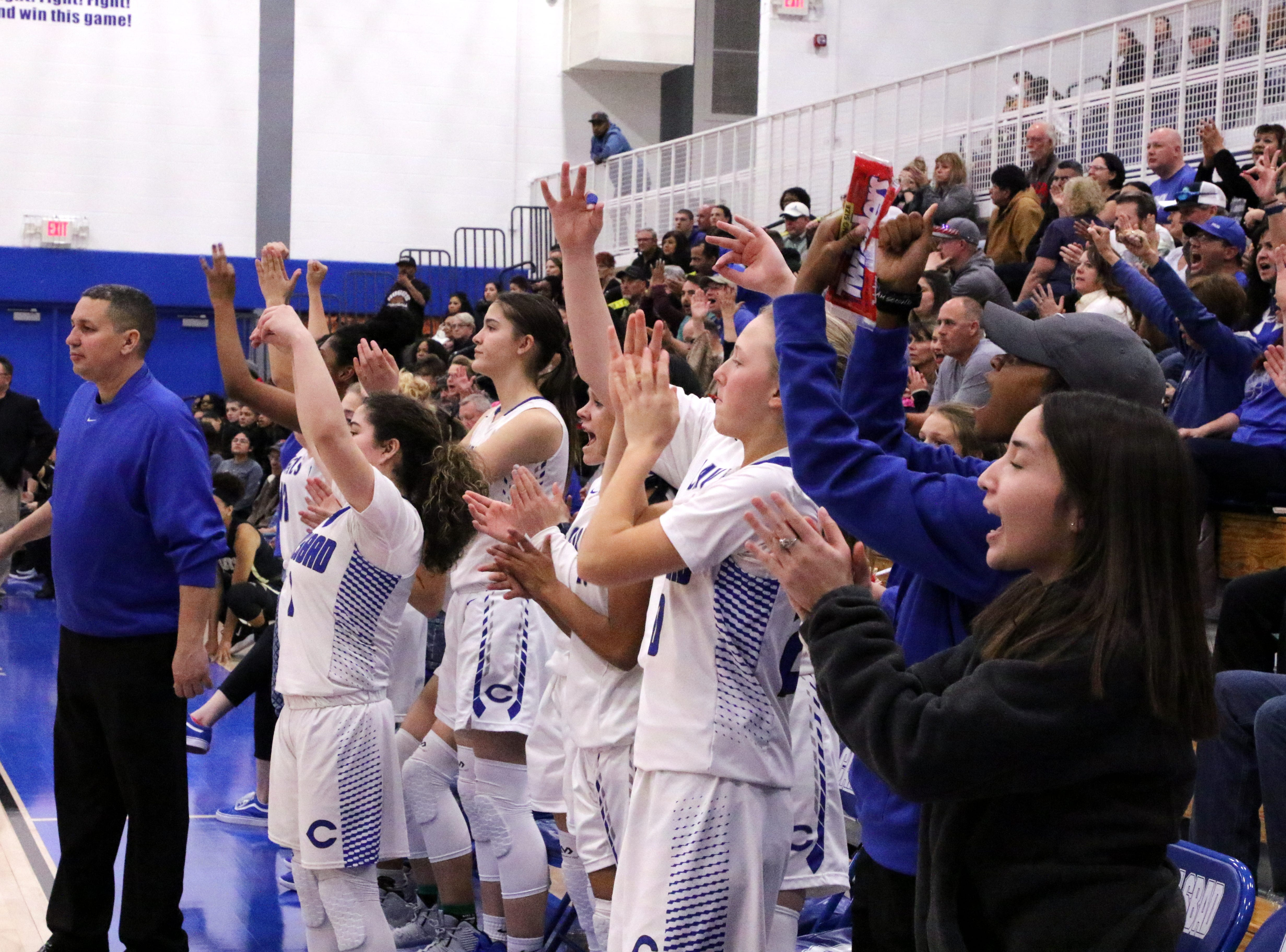 The Cavegirls bench reacts to a 3-point shot make in the second half of Friday's game against Hobbs.