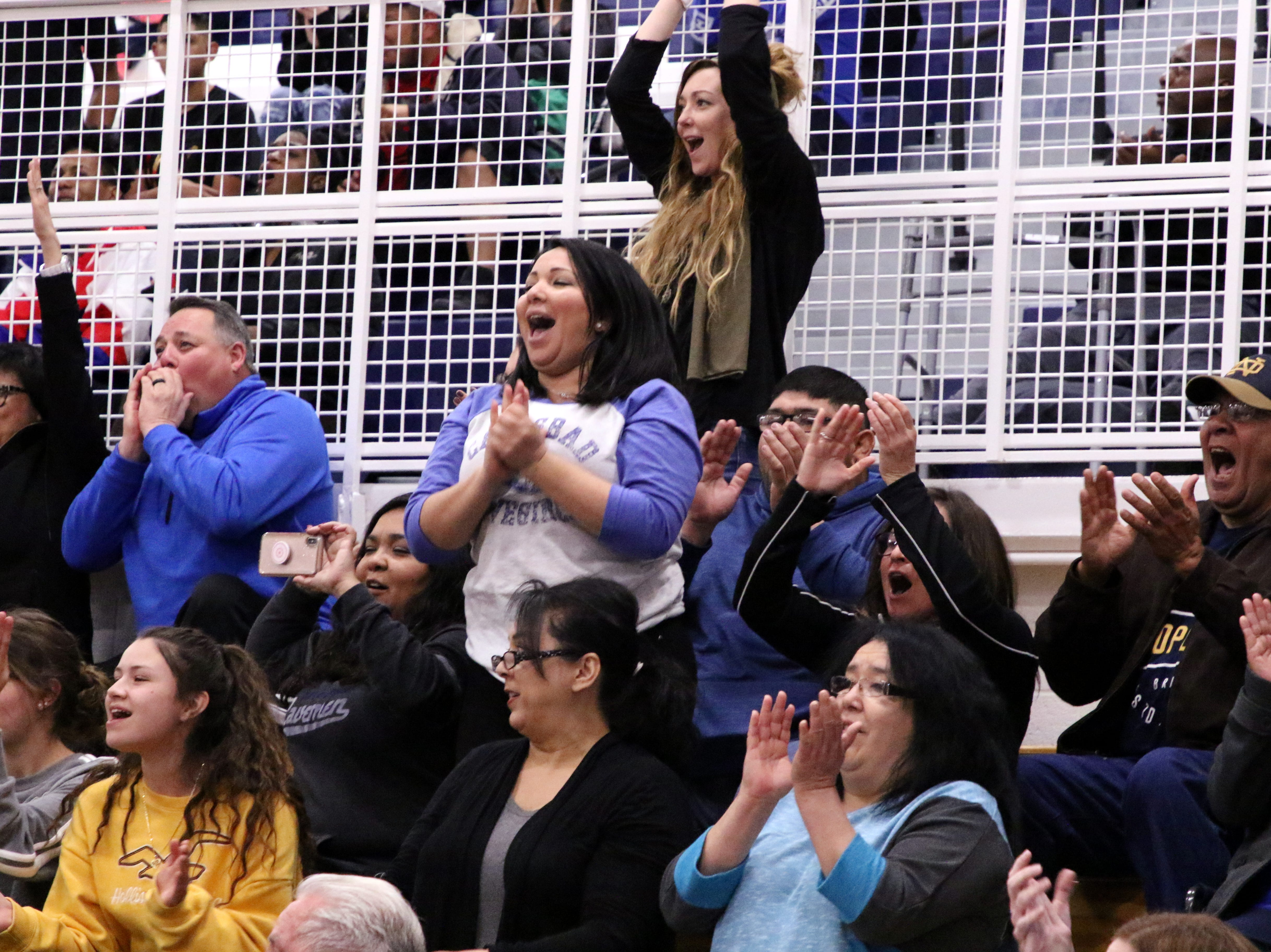 A few rowdy fans cheer after the Cavegirls made a 3-point shot in the first half of Friday's game.