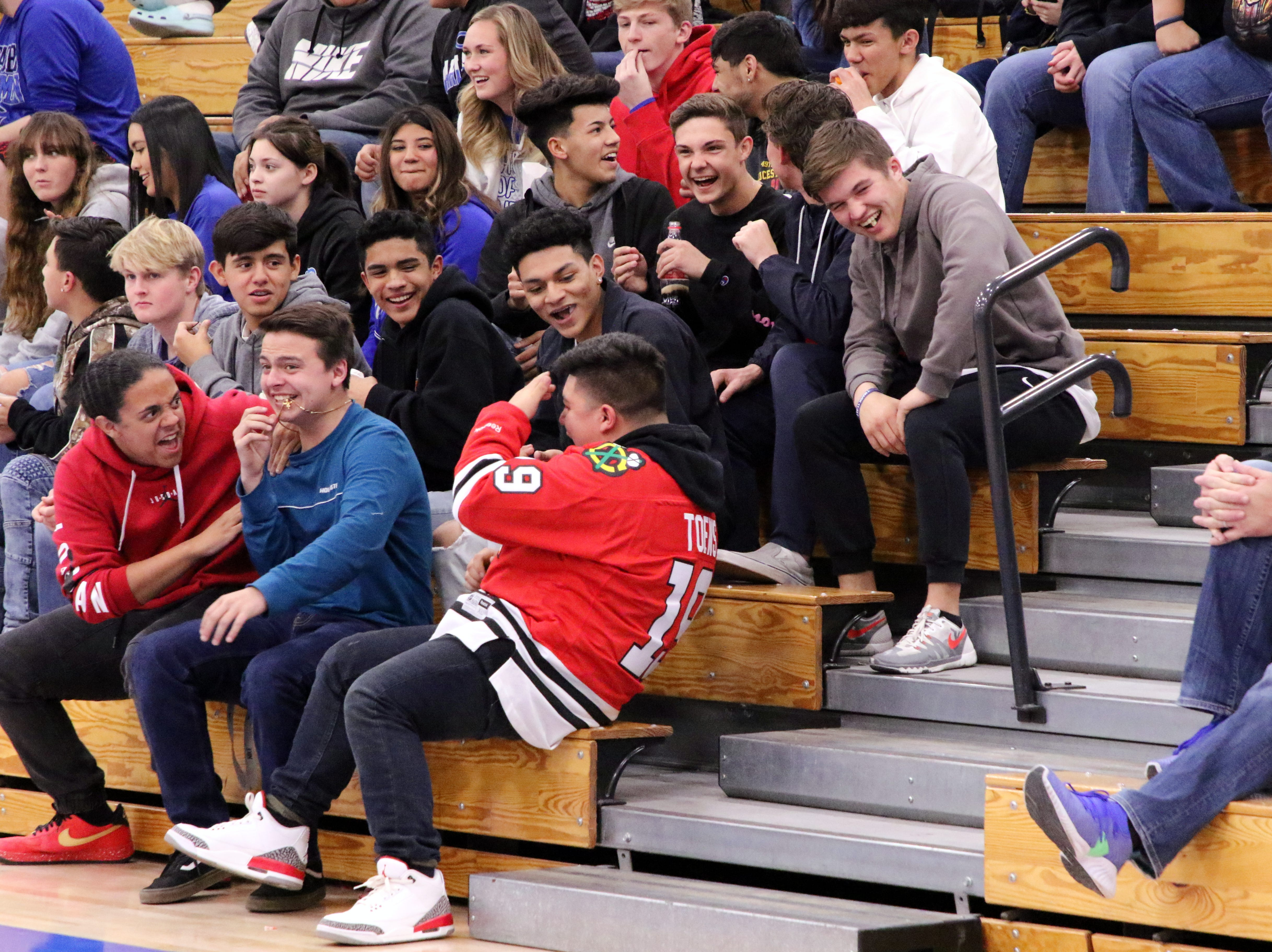 Carlsbad students laugh at a fellow student in the Chicago Blackhawks jersey after he was hit in the face with a basketball during Friday's game. He was looking at his phone when the ball smacked him in the head. No injuries were reported.