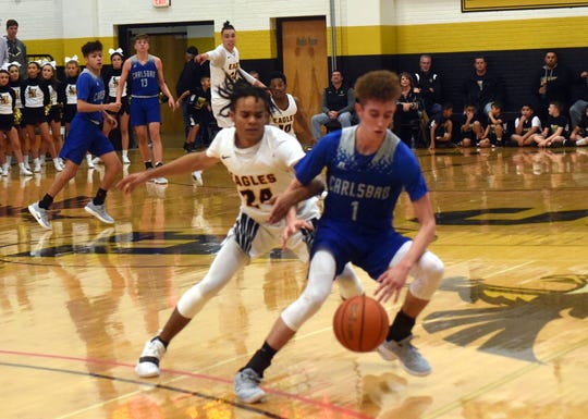 Josh Sillas works his way around Hobbs' Brundon Pettit Friday night during the first quarter of a District 4-5A basketball game in Tasker Arena. Silas led all scorers with 34 points, but the Cavemen lost 85-70 to the Eagles.