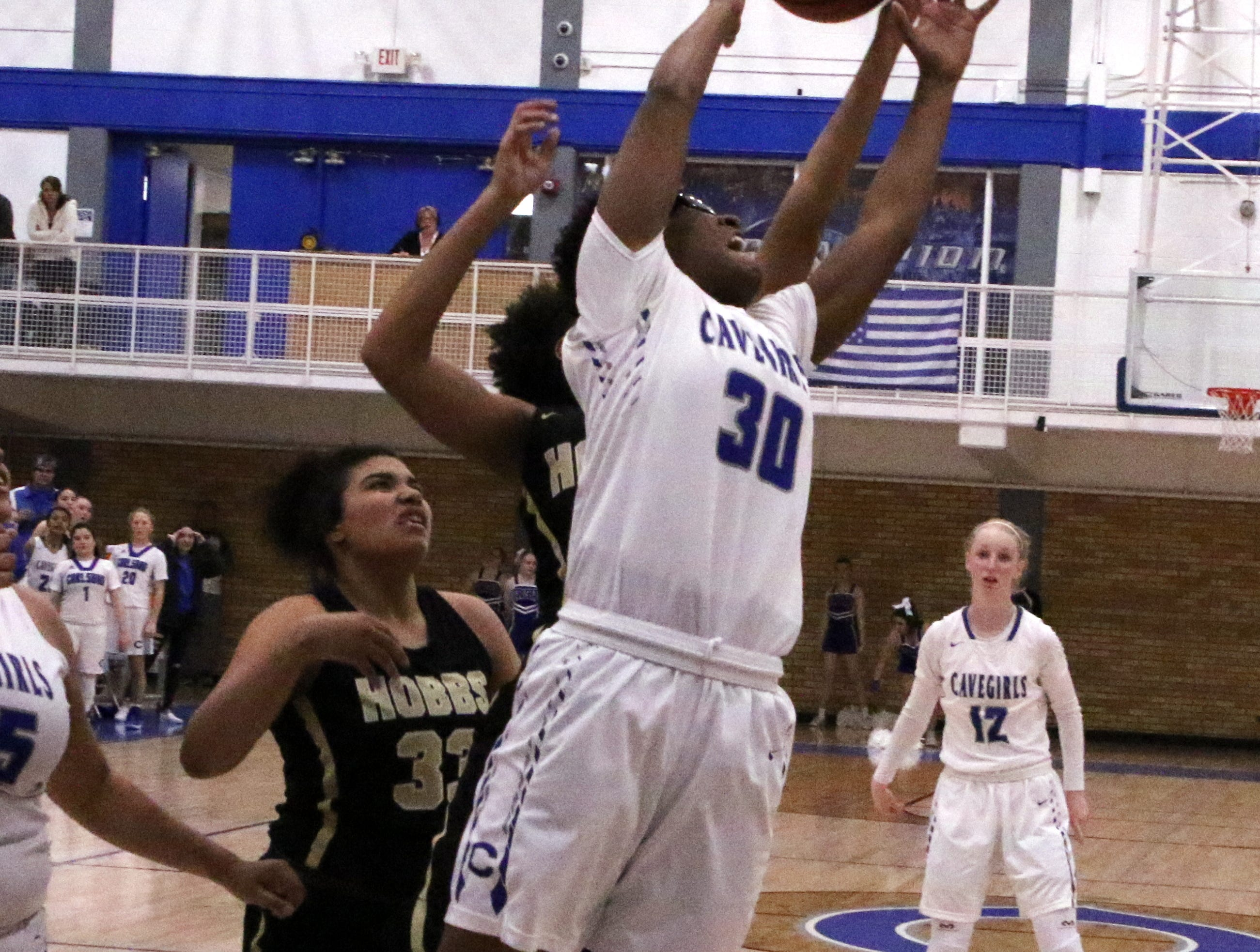 Carlsbad's Dayshaun Moore (30) collects one of her six rebounds during Friday's game against Hobbs.