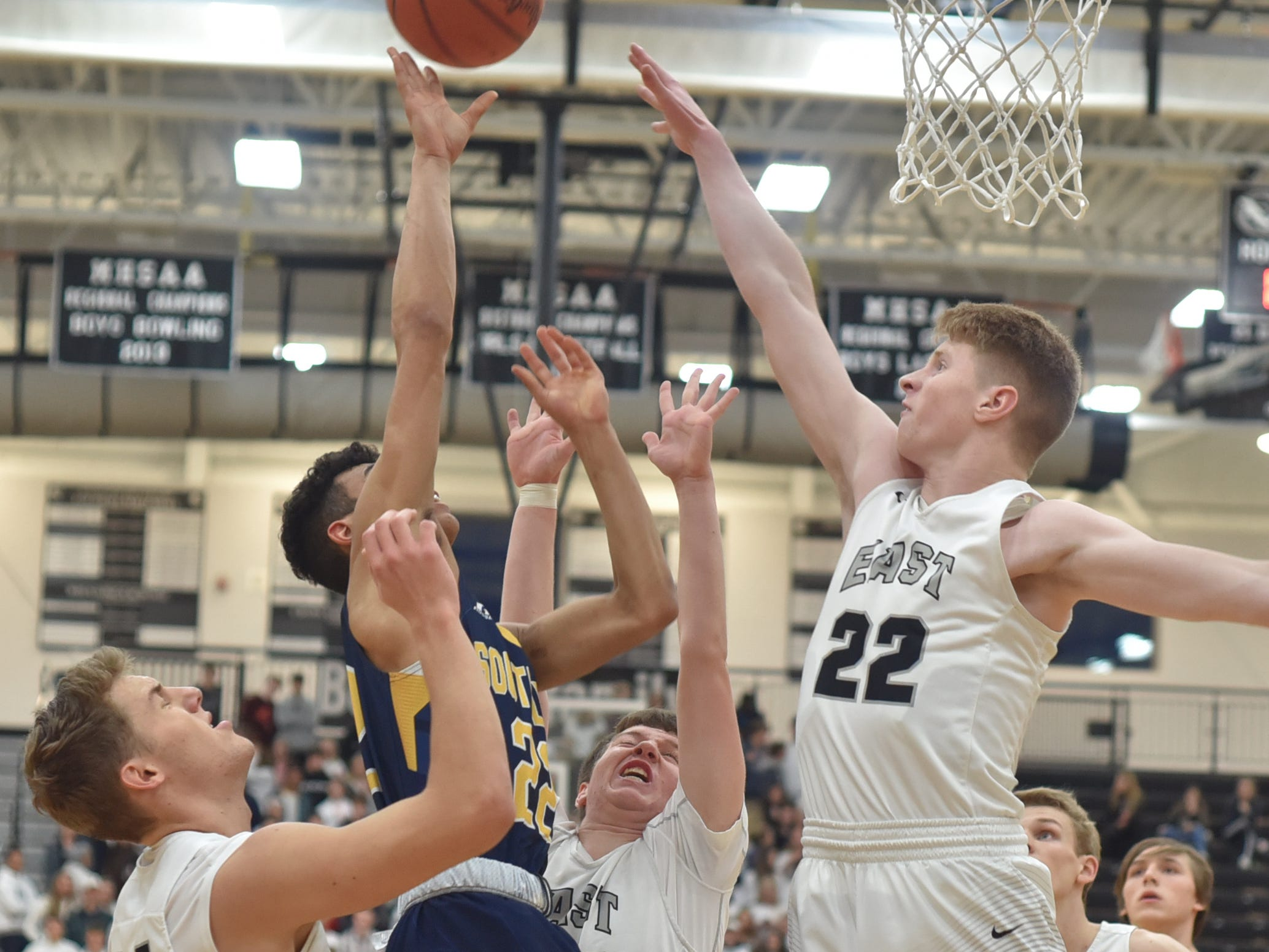 South Lyon Lion Lucas Doty runs into some issues near the basket including Cougars Chris Kaminski, left, and Drake Willlenborg, right.