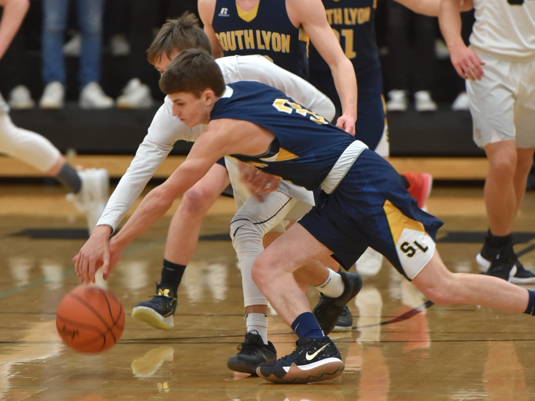 South Lyon East Cougar Sean Clary, rear, and South Lyon's Matthew Sherry go after a loose ball during the teams' Feb. 8 game.