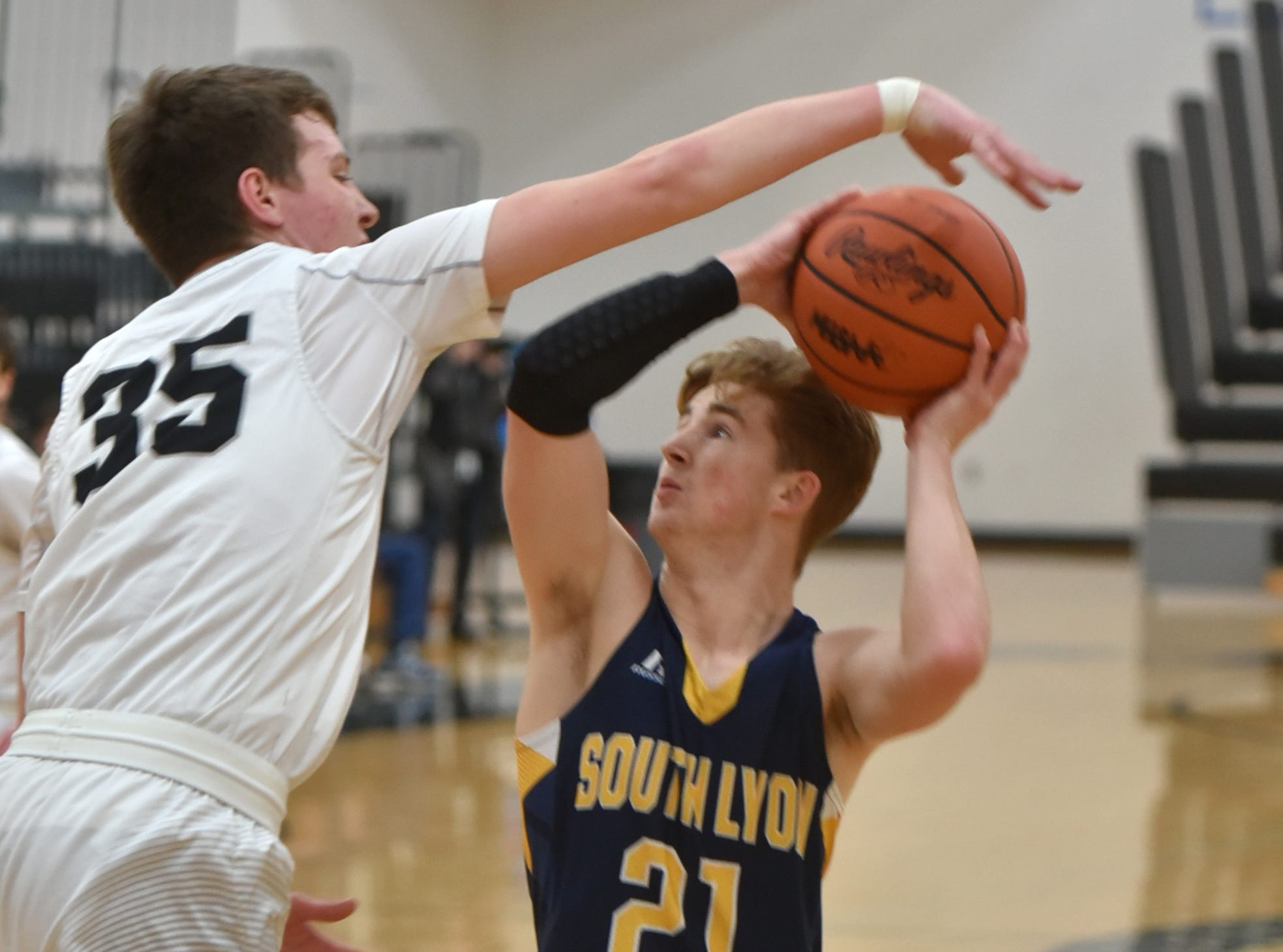 South Lyon East's Adam Trent, left, tries to block a shot by South Lyon's Connor Fracassi.