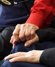 Bill, 95, and Helen Barz, 92, hold hands at their West Bloomfield home.