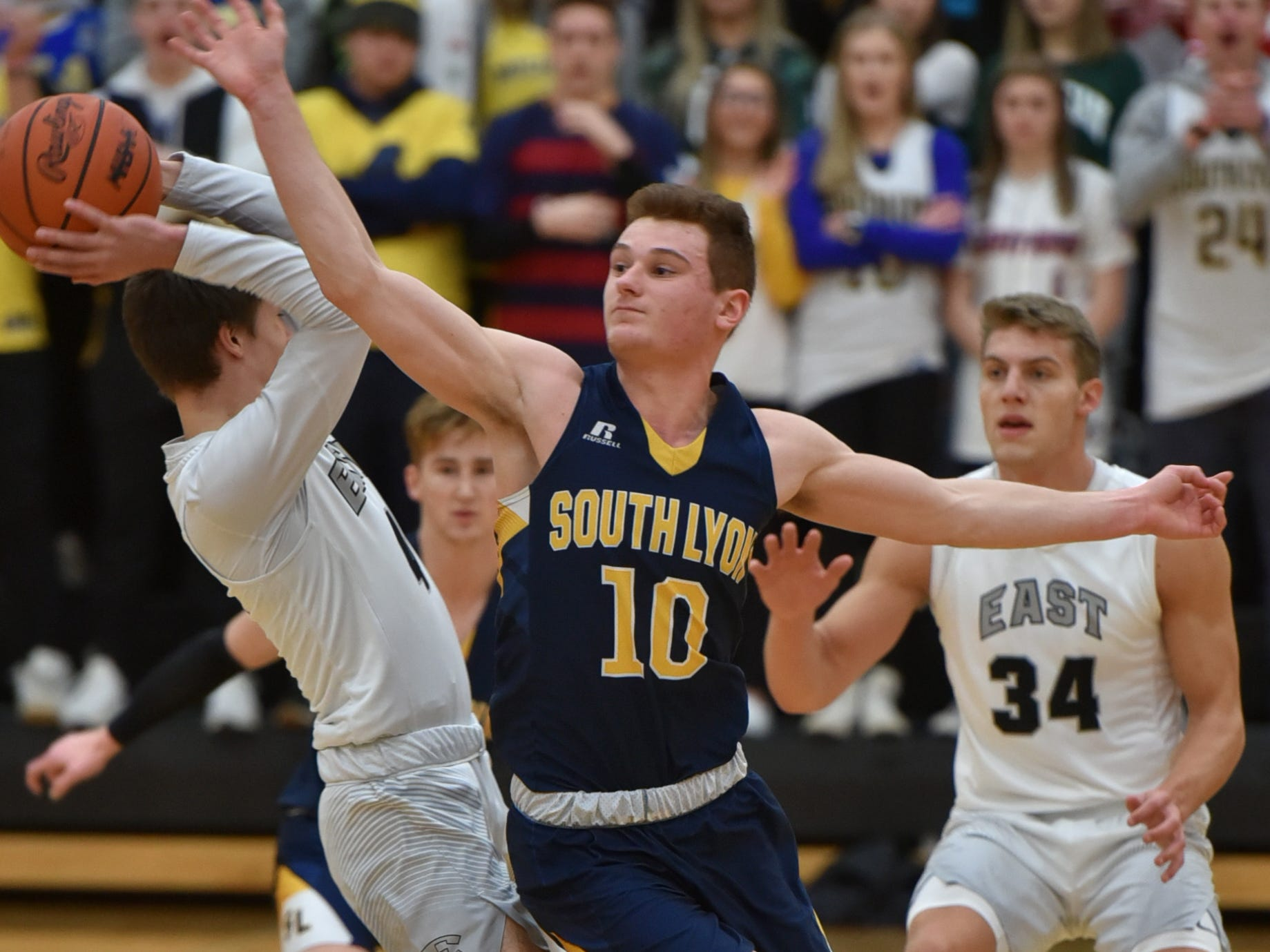 South Lyon Lion Owen Deline puts some pressure on South Lyon East Cougar Sean Clary, left.