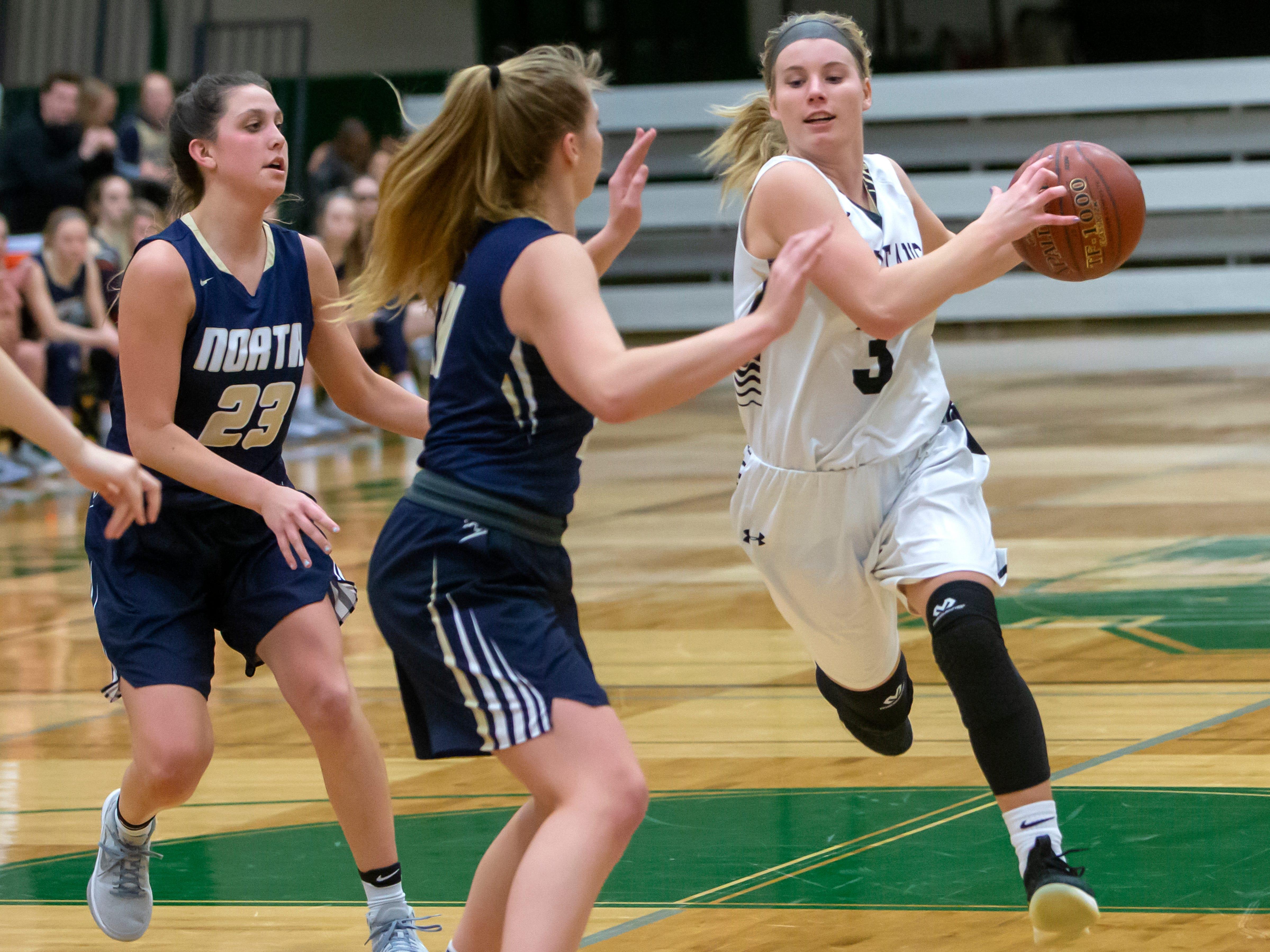 Oshkosh North's Ashley Wissink charges toward the basket around Appleton North's Paige Schabo at the girls basketball game Friday, February 8, 2019, in Oshkosh, Wis., at Oshkosh North High School.