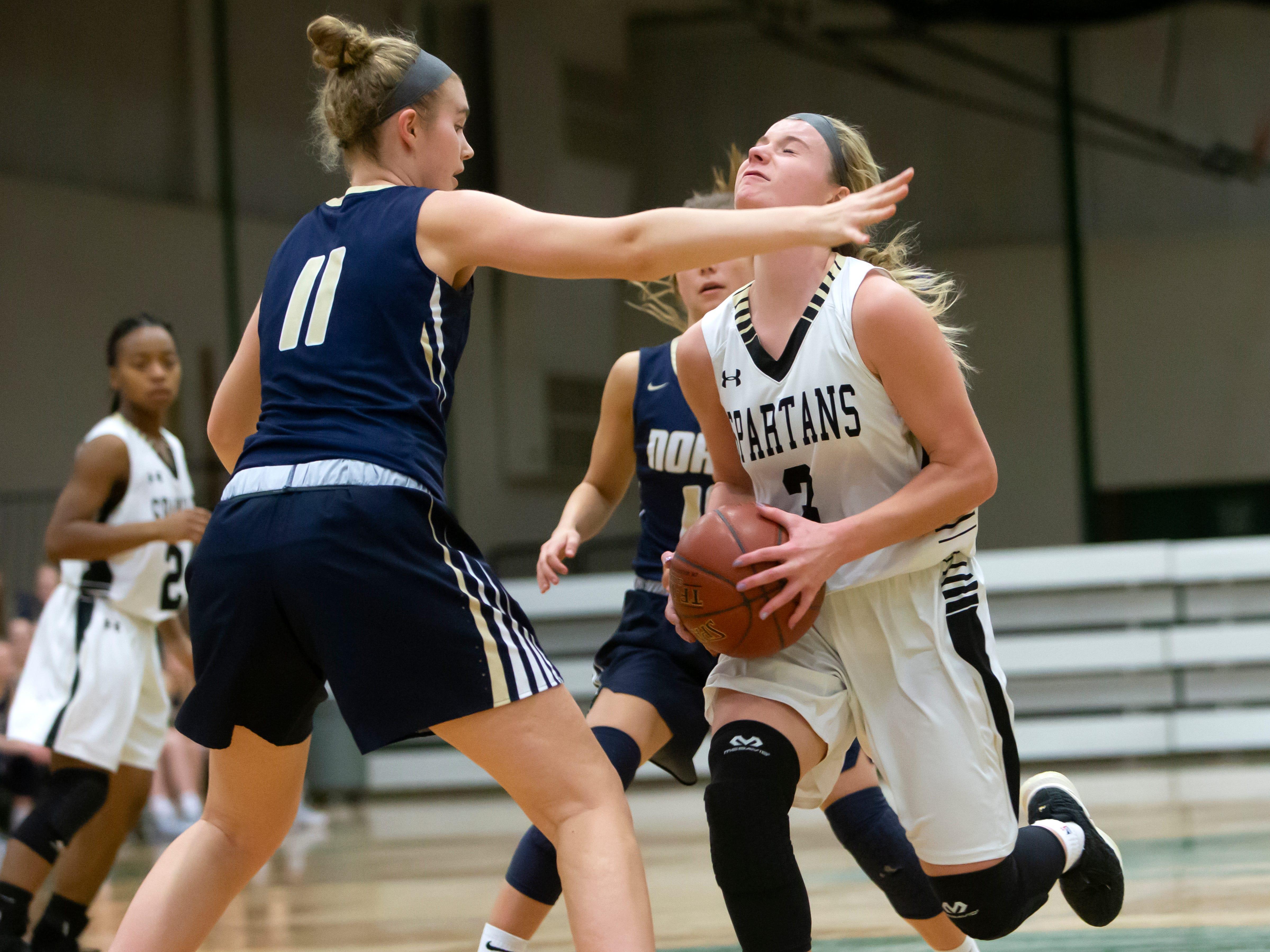 Appleton North's Emma Erickson blocks Ashley Wissink of Oshkosh North rush to the basket during a girls basketball game Friday, February 8, 2019, in Oshkosh, Wis., at Oshkosh North High School.