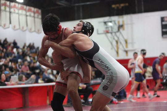 Palm Desert High School's Troy Mantanona, in black cap, wrestles with Alex Godina of Westminster during their semifinal match at Palm Springs, High School on February 9, 2019.