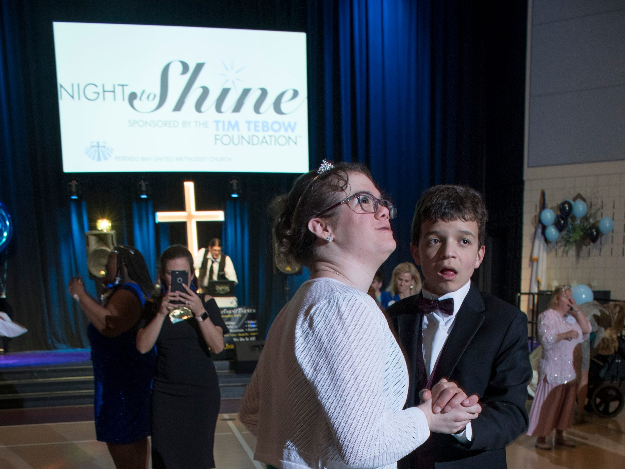 Haylee Andrews peeks up a her family as she dances with Riley Stevens during the Night to Shine prom for people with special needs sponsored by the Tim Tebow Foundation at Perdido Bay United Methodist Church in Pensacola on Friday, February 8, 2019.
