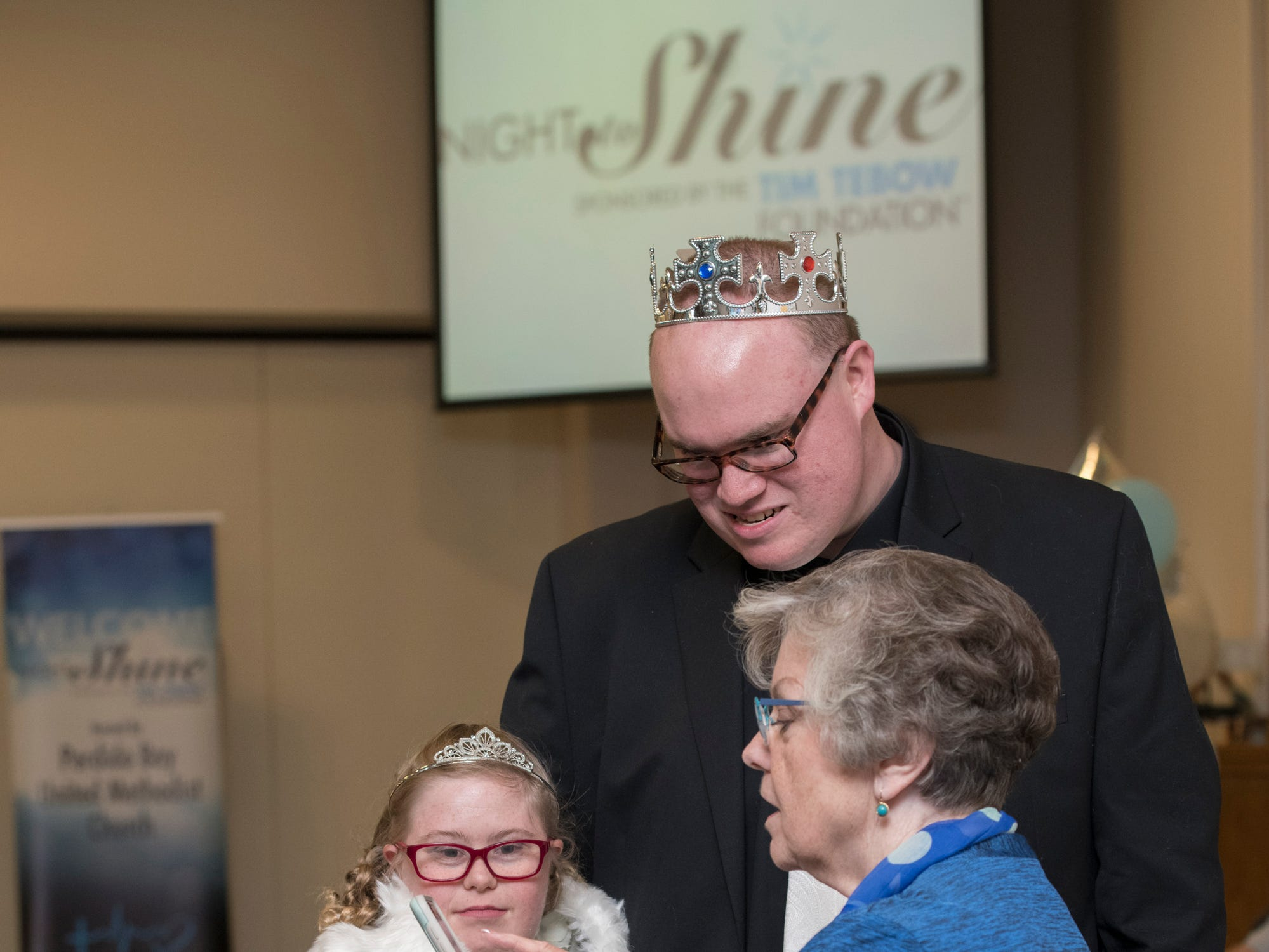 Kaitlyn Evans and Shawn Brown check out a photo of themselves on a phone at the beginning of the Night to Shine prom for people with special needs sponsored by the Tim Tebow Foundation at Perdido Bay United Methodist Church in Pensacola on Friday, February 8, 2019.