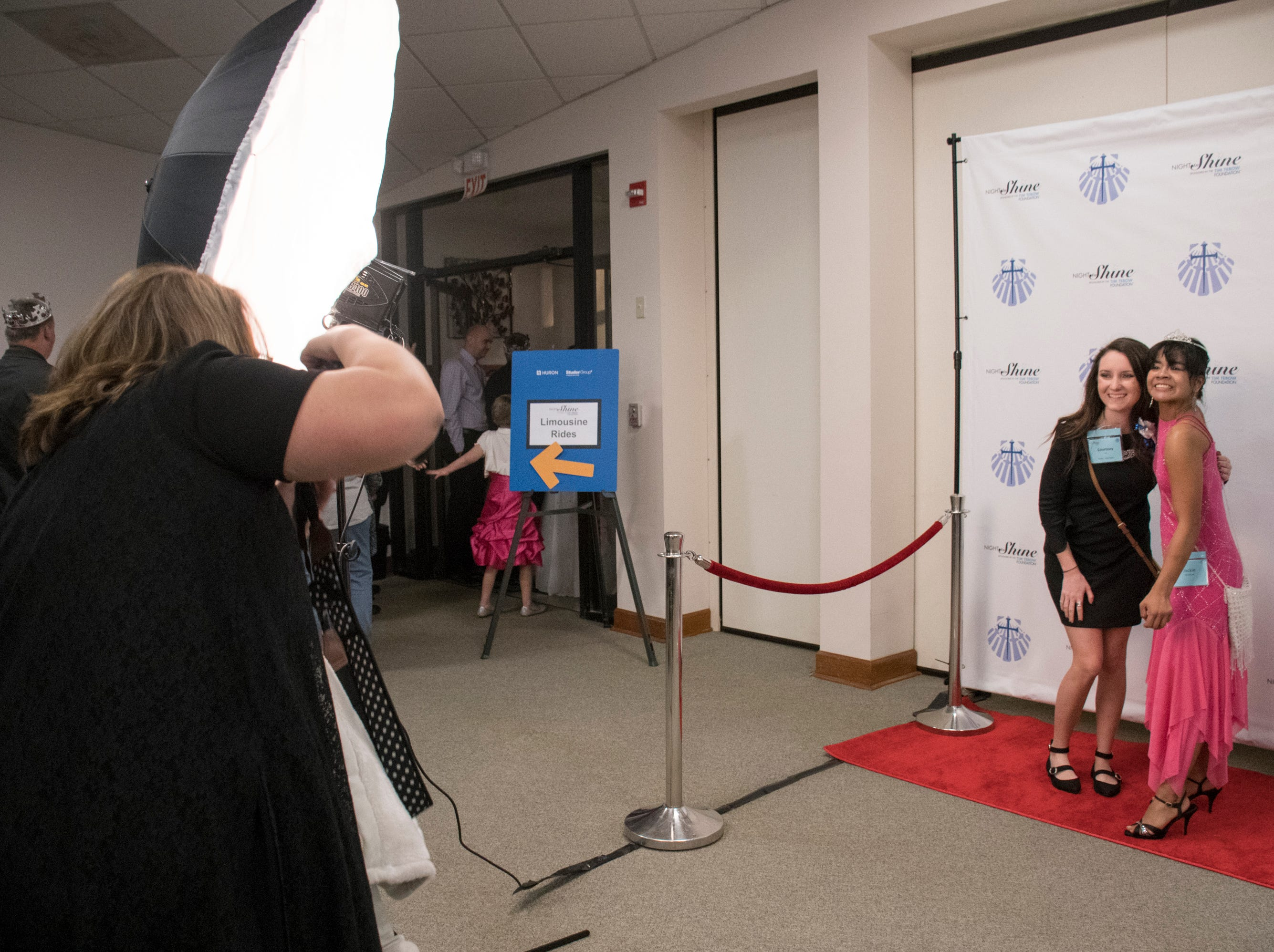 Courtney Hall, left, and Jackie Hunnicutt get their photo taken at the beginning of the Night to Shine prom for people with special needs sponsored by the Tim Tebow Foundation at Perdido Bay United Methodist Church in Pensacola on Friday, February 8, 2019.