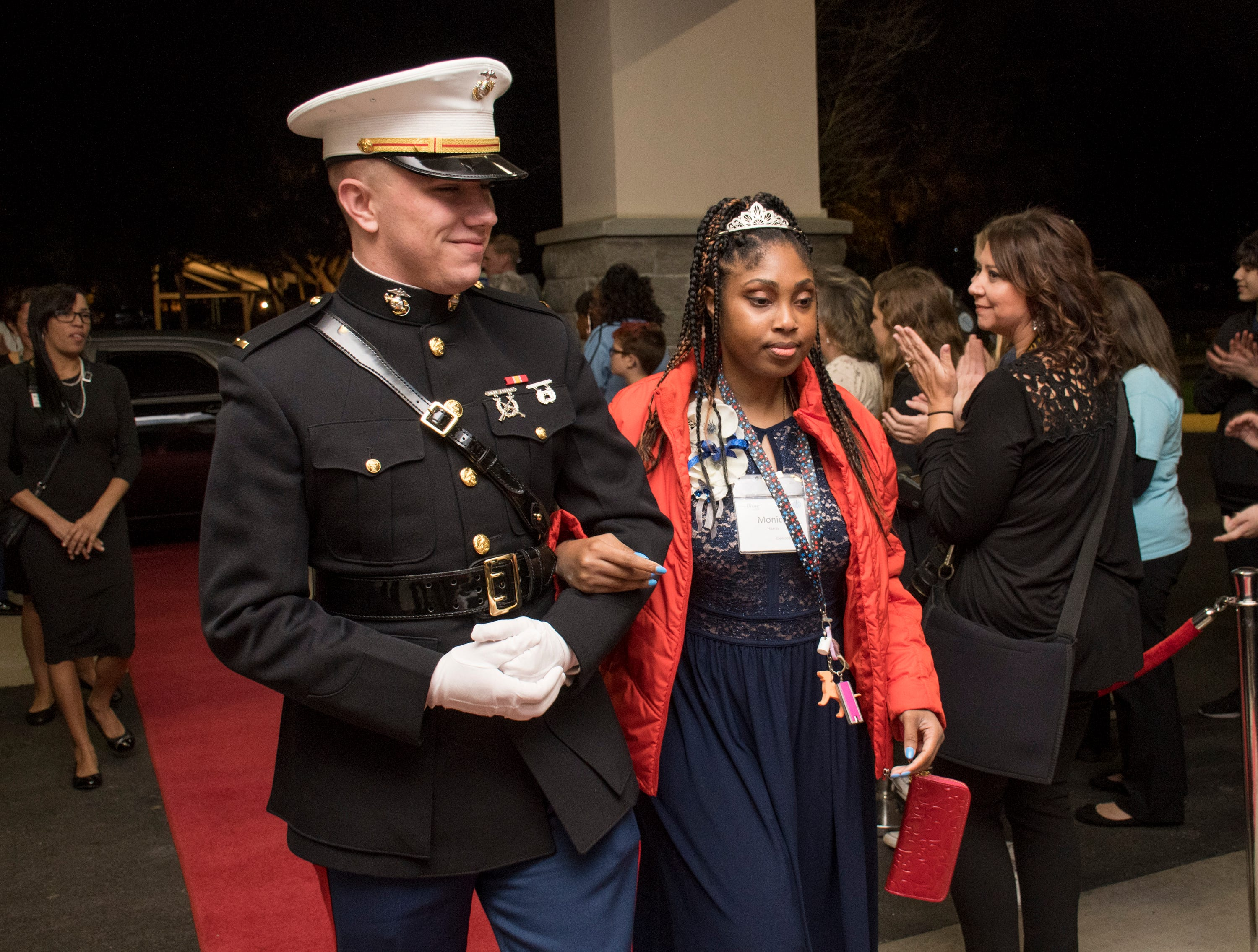 US Marine 2nd Lt. Nathan Sturgeon escorts Monica Harris into the Night to Shine prom for people with special needs sponsored by the Tim Tebow Foundation at Perdido Bay United Methodist Church in Pensacola on Friday, February 8, 2019.