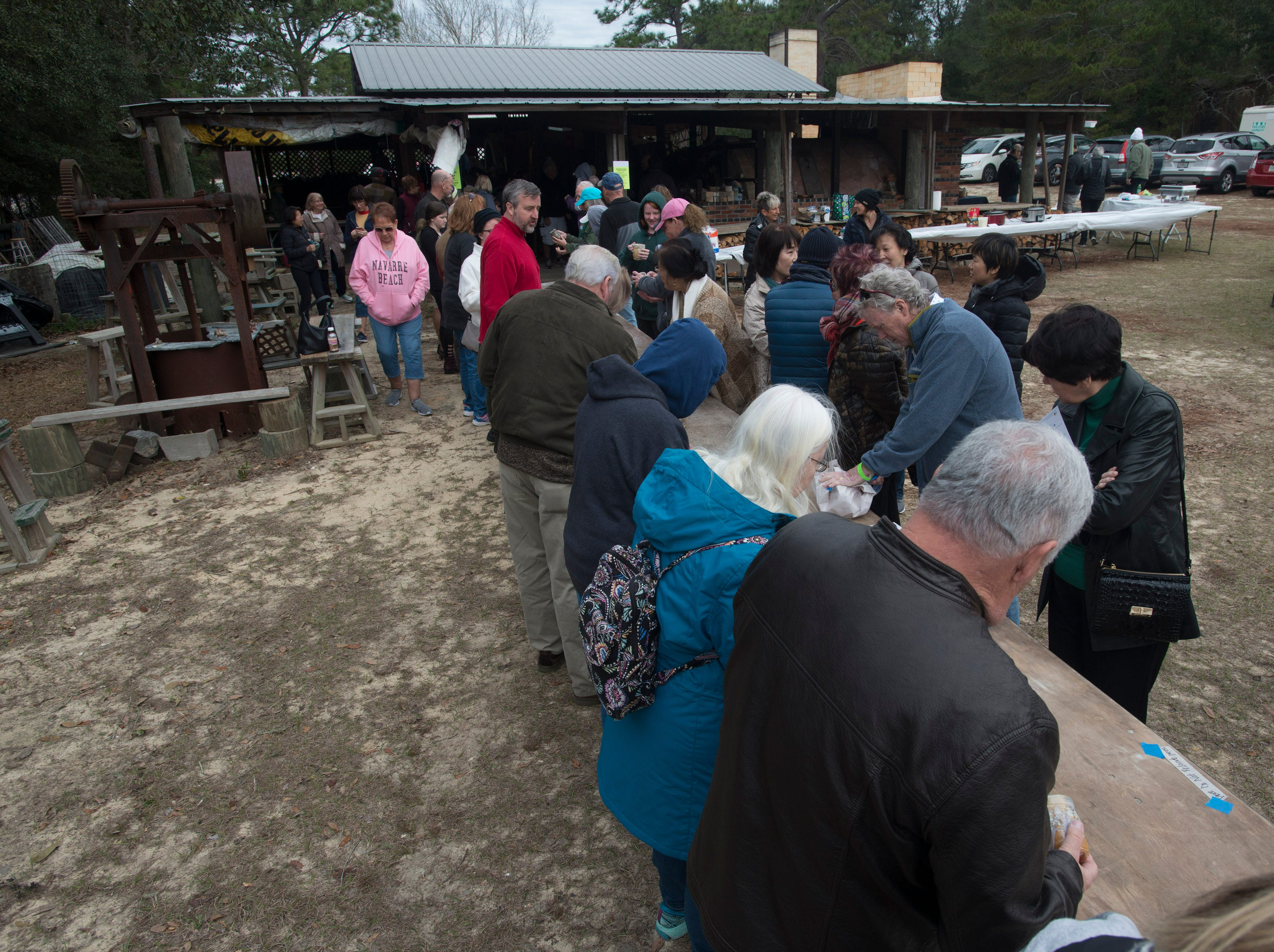 The public checks out pottery being unloaded from the kiln Saturday, February 9, 2019, during the 14th annual Woodstoke Pottery and Kiln Festival at Holly Hill Pottery in Navarre.