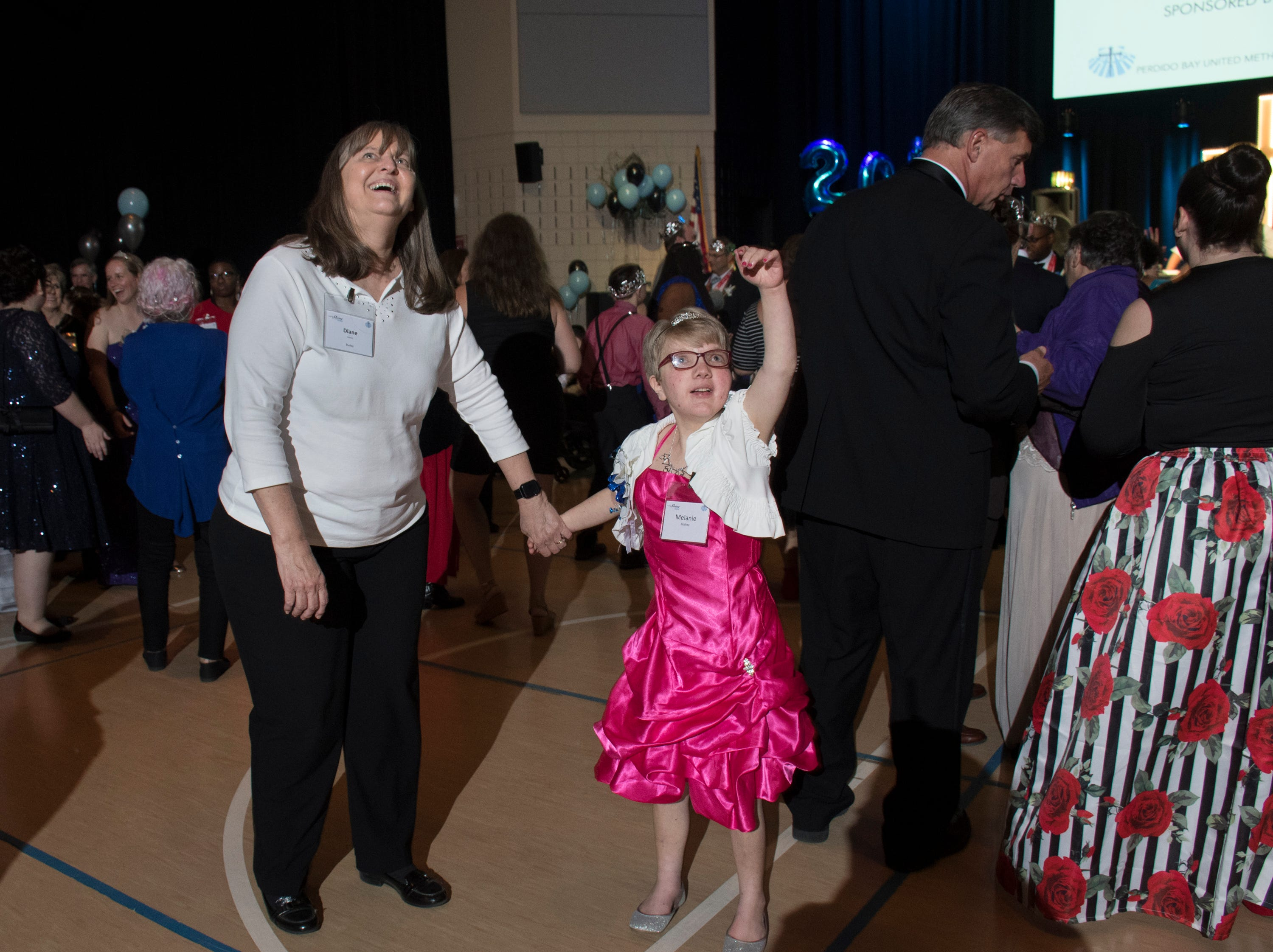 Melanie Bushey waves to her family as she dances with her buddy Diane during the Night to Shine prom for people with special needs sponsored by the Tim Tebow Foundation at Perdido Bay United Methodist Church in Pensacola on Friday, February 8, 2019.