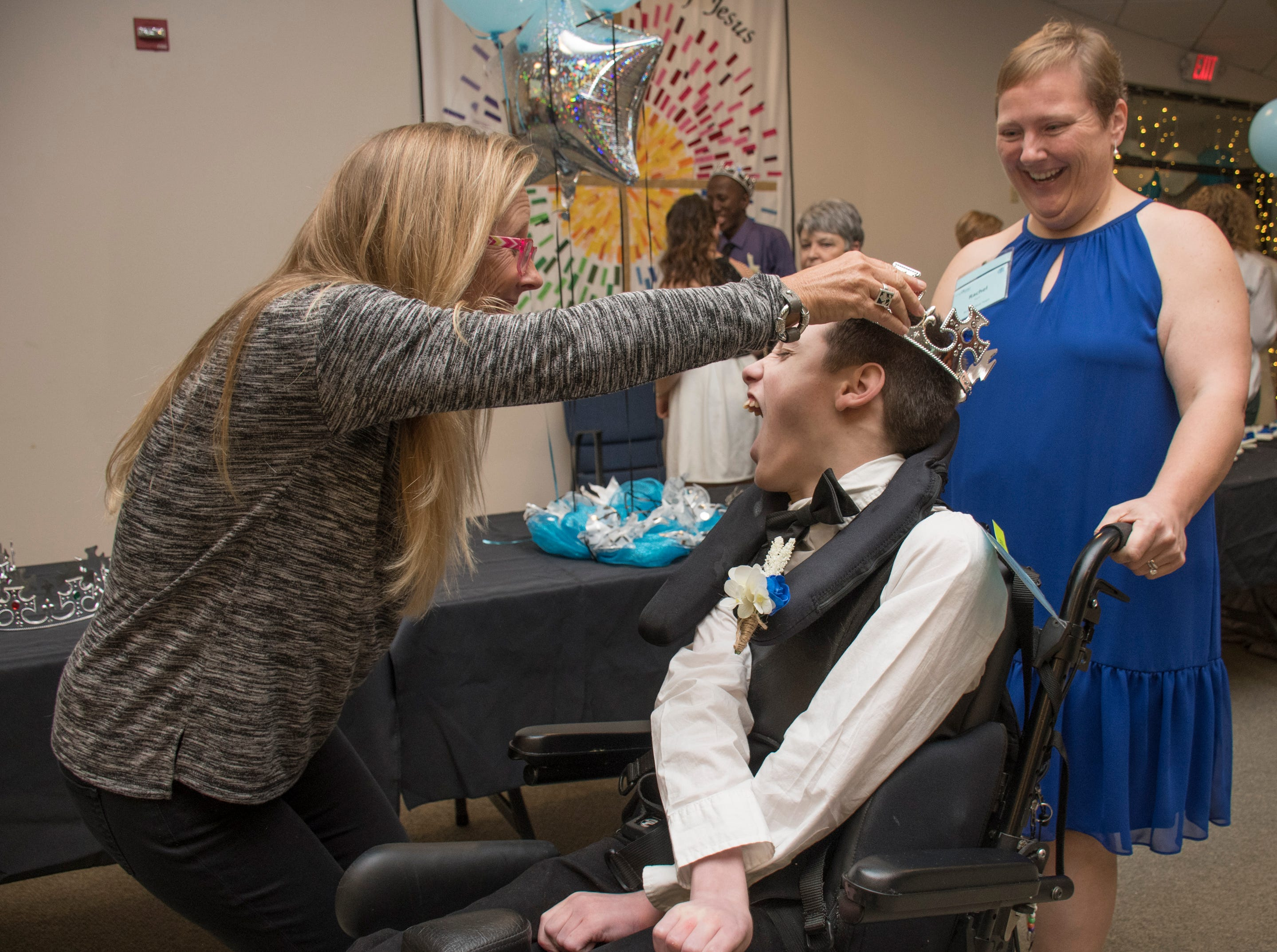 Samuel Wilkie is all smiles as Marcy Costa places a crown on his head at the beginning of the Night to Shine prom for people with special needs sponsored by the Tim Tebow Foundation at Perdido Bay United Methodist Church in Pensacola on Friday, February 8, 2019.