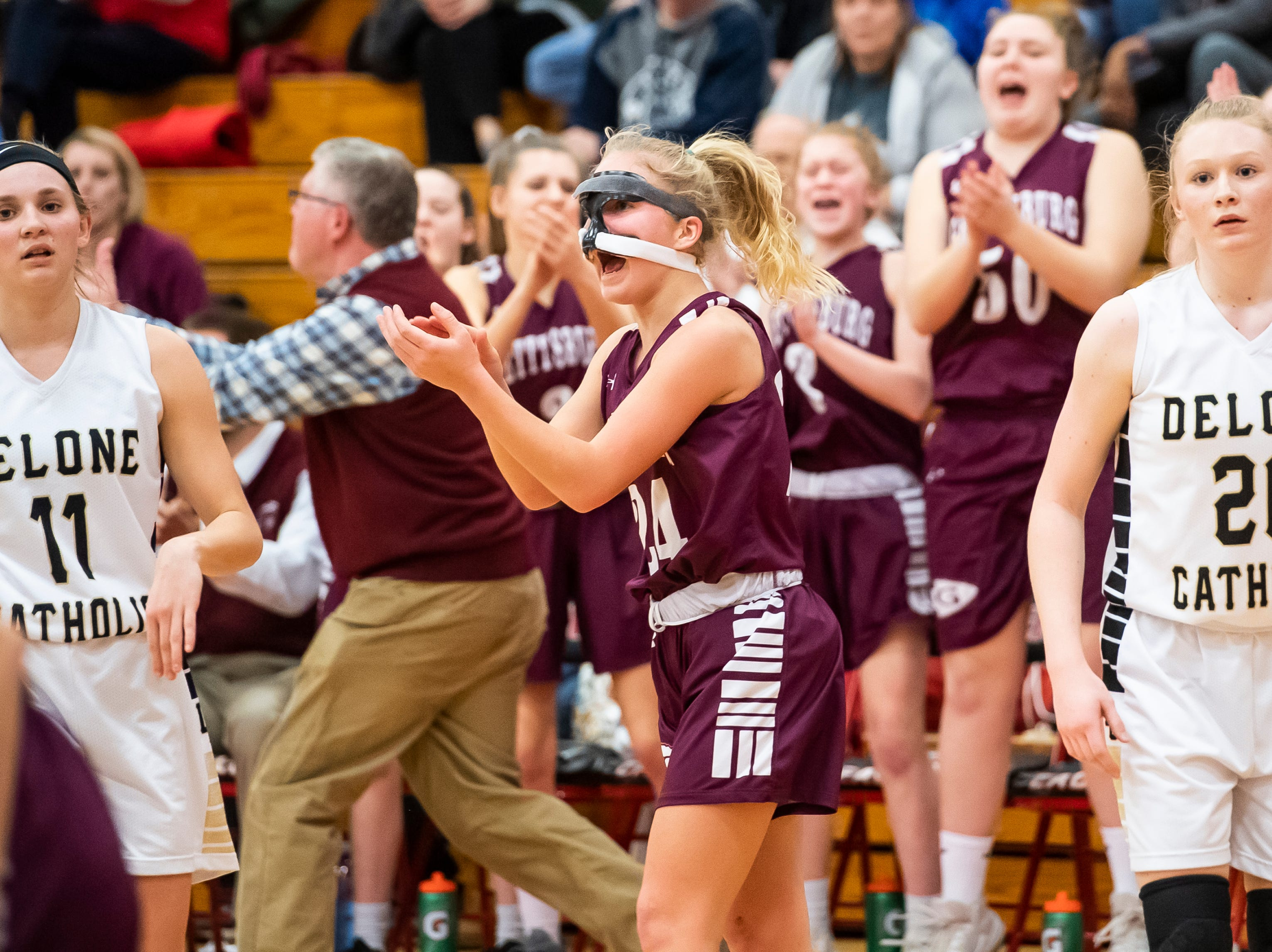 Gettysburg's Anne Bair, center, claps after the Warriors score a layup late in the fourth quarter of play against Delone Catholic in a YAIAA quarterfinal game at Dover High School Friday, February 8, 2019.