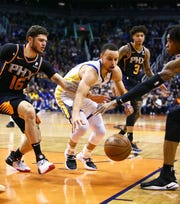 Phoenix Suns guard Tyler Johnson (16) knocks the ball away from Golden State Warriors guard Stephen Curry in the second half on Feb. 8 at Talking Stick Resort Arena.