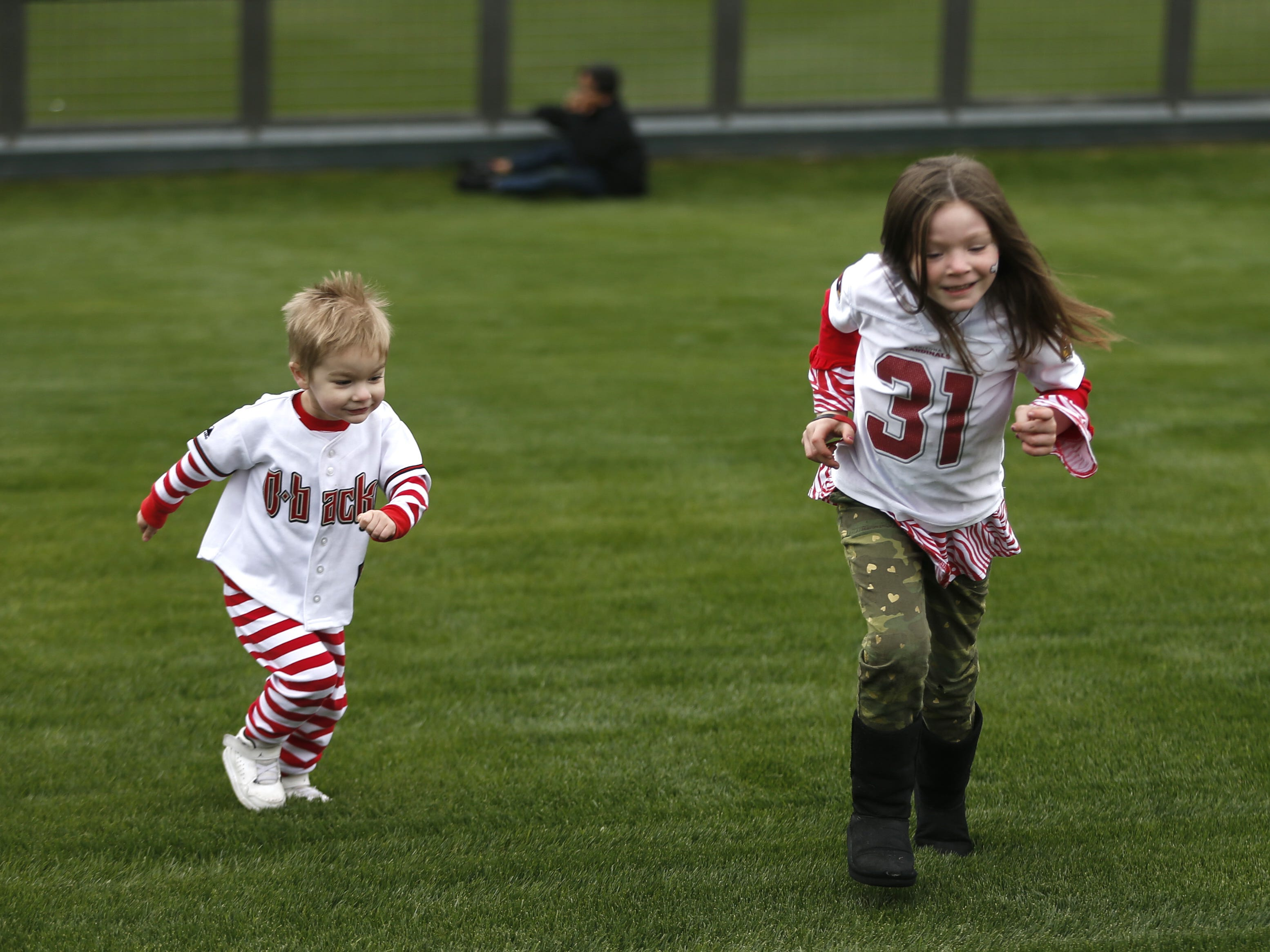Atlas Palmer, 2, and his sister Aurora Palmer run up the green berm during the Diamondbacks Fan Fest at Salt River at Talking Sticks on February 9, 2019.