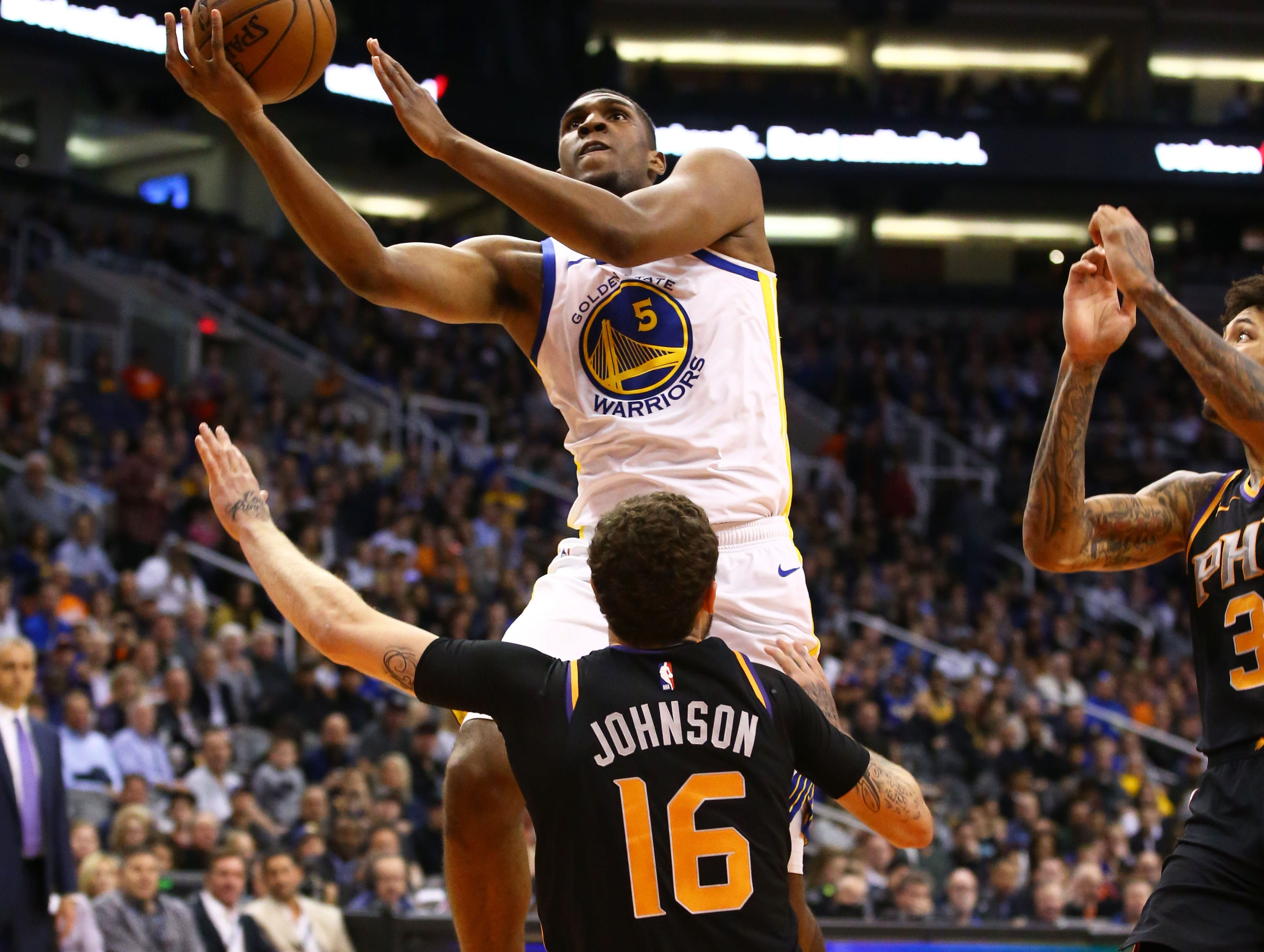 Phoenix Suns guard Tyler Johnson takes the charge by Golden State Warriors center Kevon Looney in the second half on Feb. 8 at Talking Stick Resort Arena.