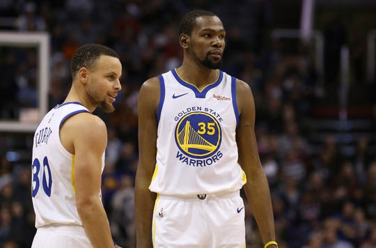 Golden State Warriors guard Stephen Curry (30) and forward Kevin Durant (35) pause during the first half of an NBA basketball game against the Phoenix Suns Friday, Feb. 8, 2019, in Phoenix. The Warriors defeated the Suns 117-107. (AP Photo/Ross D. Franklin)