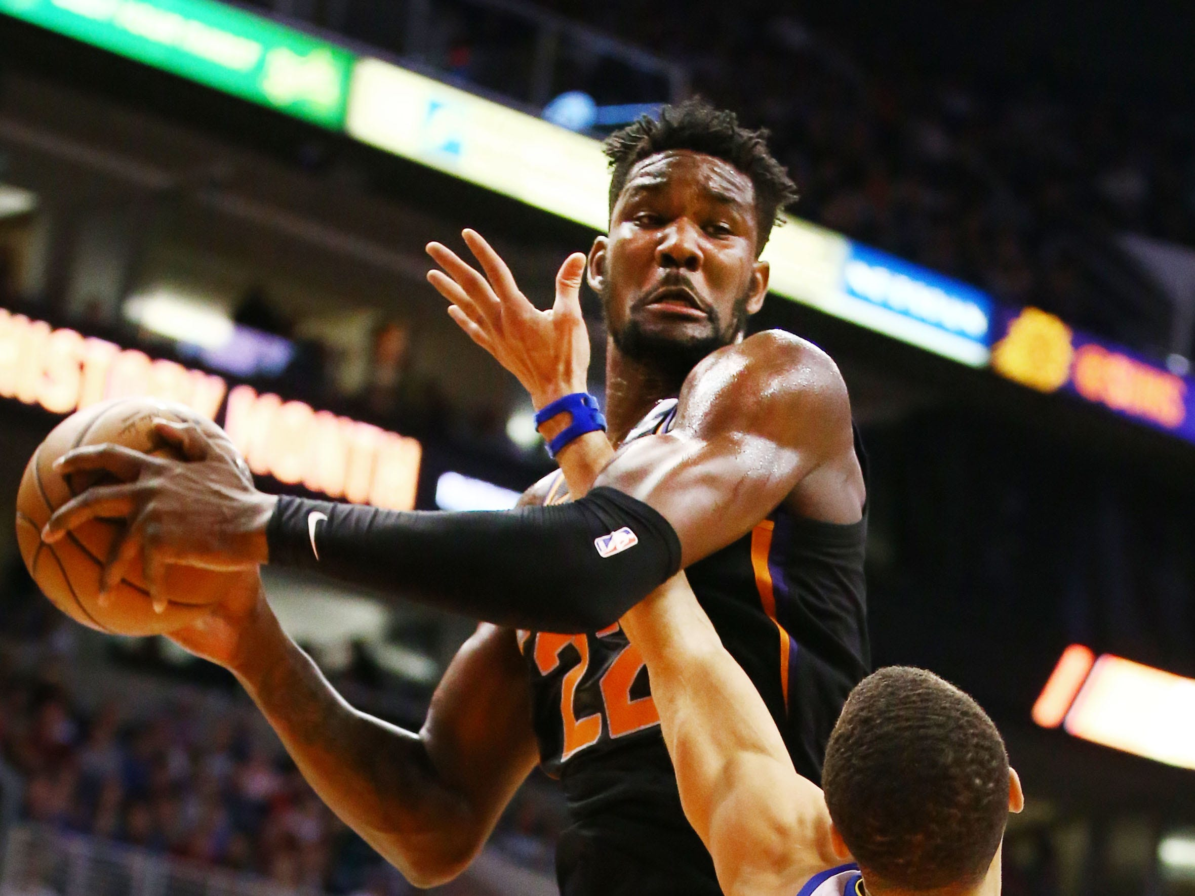 Phoenix Suns center Deandre Ayton is pressured by Golden State Warriors guard Stephen Curry in the first half on Feb. 8 at Talking Stick Resort Arena.