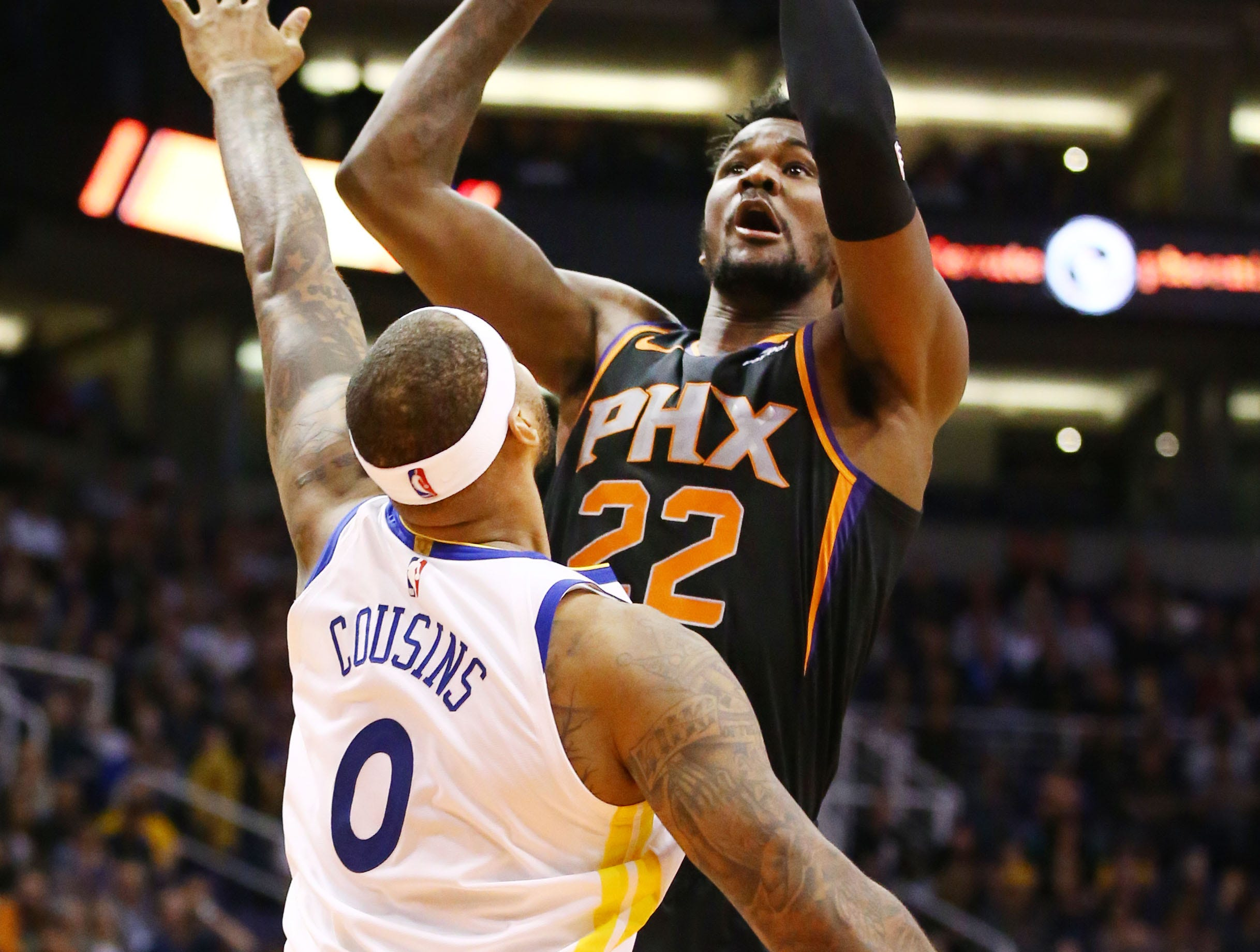 Phoenix Suns center Deandre Ayton takes a shot over Golden State Warriors center DeMarcus Cousins in the first half on Feb. 8 at Talking Stick Resort Arena.