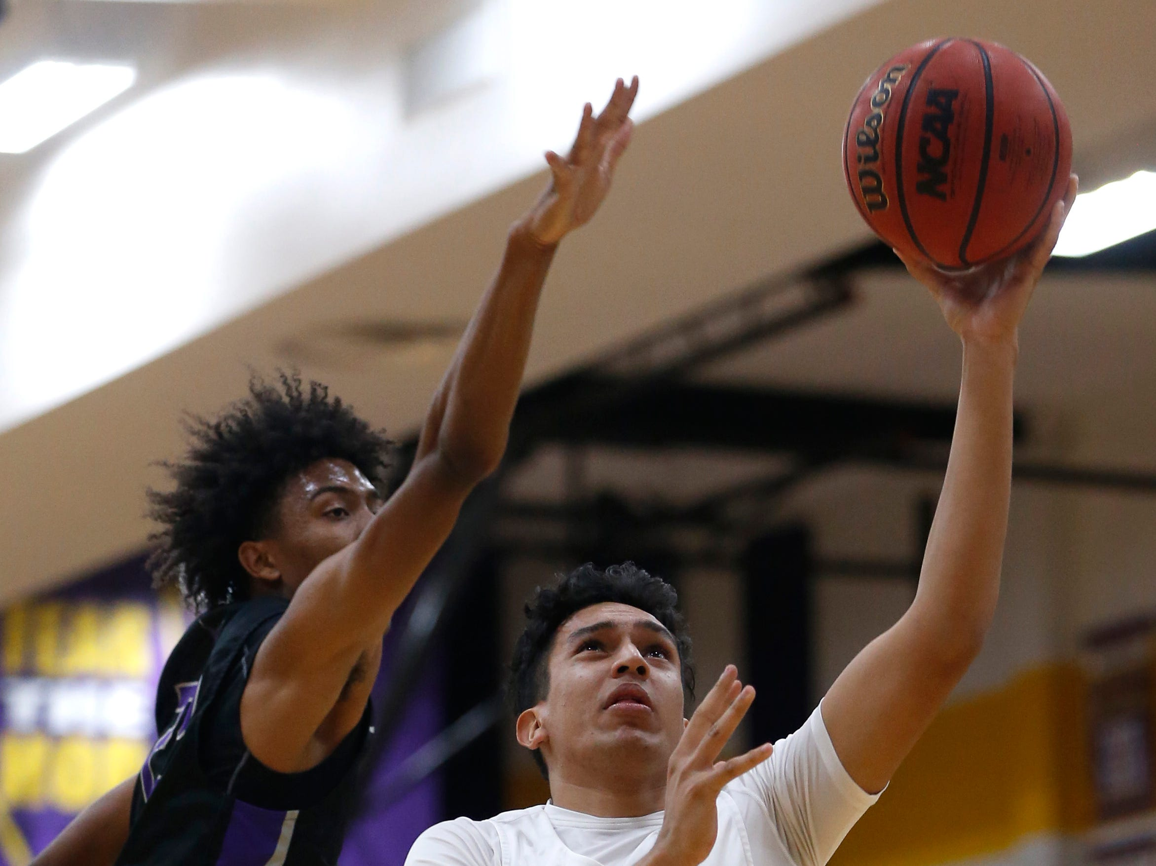 Mesa's Jesus Velazco (43) makes a layup past Valley Vista's Curtis Nichols (22) during the first half of the boys basketball tournament play-in game at Mesa High School in Mesa, Ariz. on February 8, 2019.
