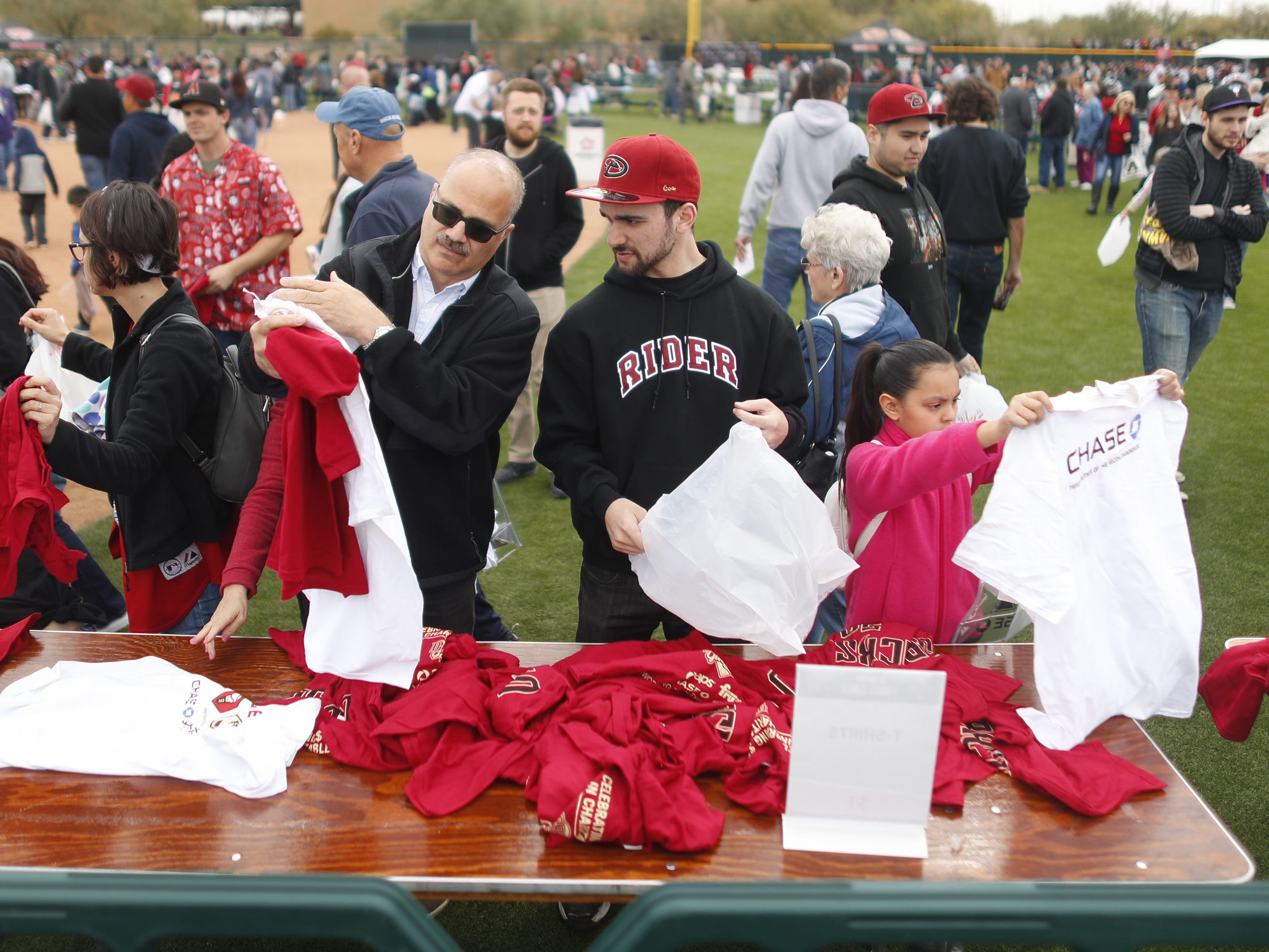 Fans look through discount merchandise on the field during the Diamondbacks Fan Fest at Salt River at Talking Sticks on February 9, 2019.