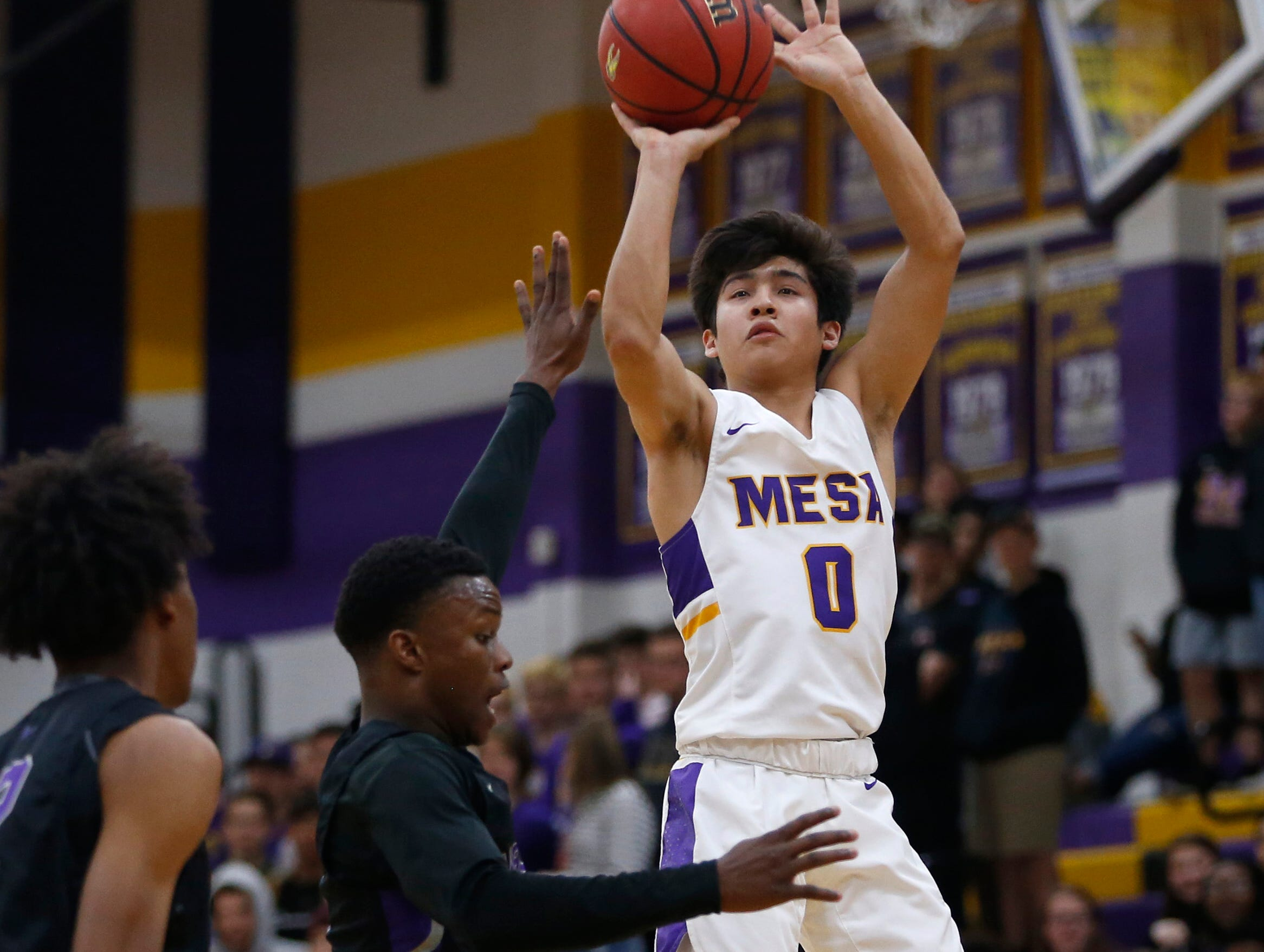 Mesa's Tony Adame (0) shoots against Valley Vista's Sidney Thomas (1) during the first half of the boys basketball tournament play-in game at Mesa High School in Mesa, Ariz. on February 8, 2019.
