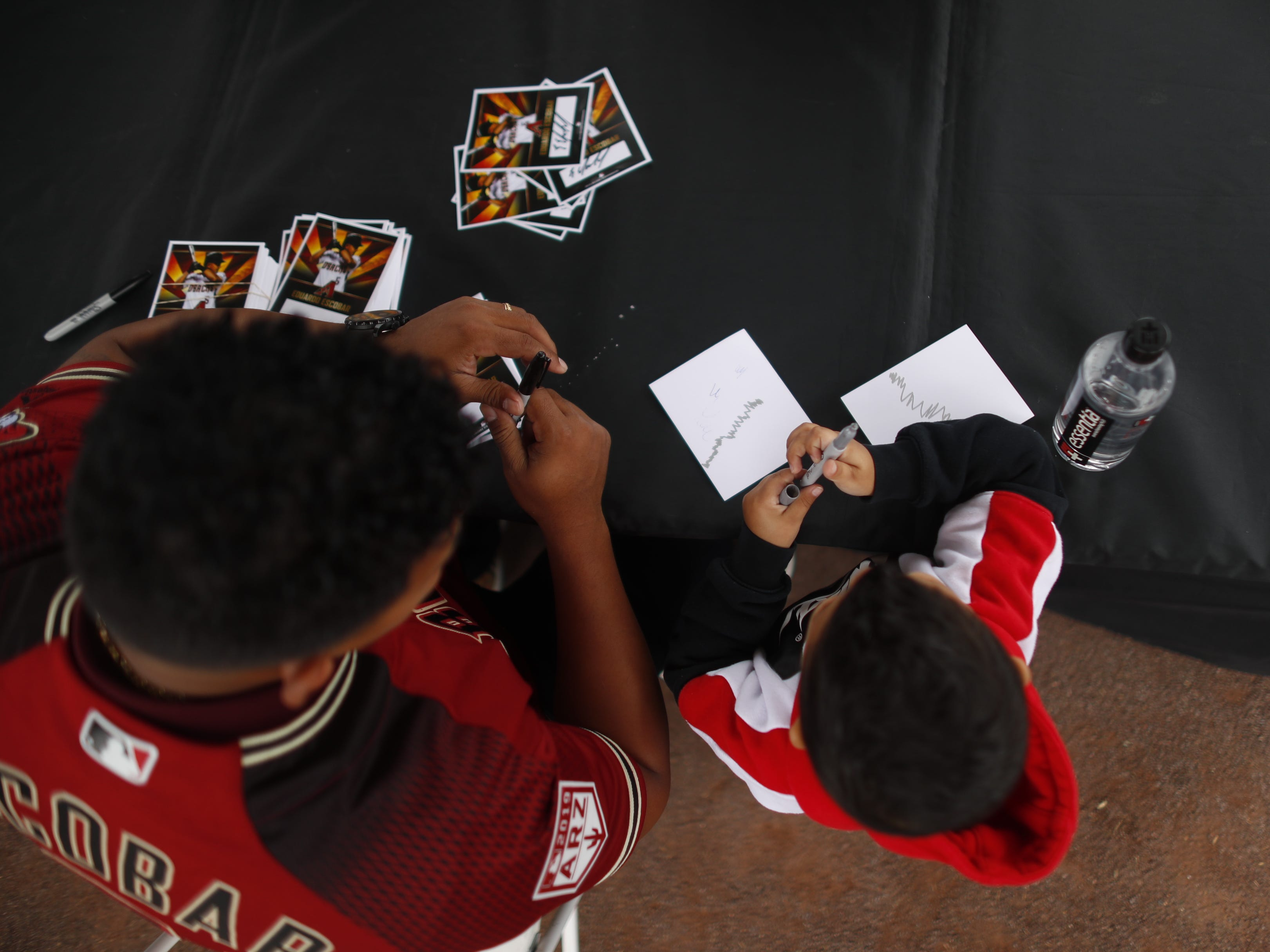 Eduardo Escobar (L) and his son Emmanuel Escobar sign autographs during the Diamondbacks Fan Fest at Salt River at Talking Sticks on February 9, 2019.