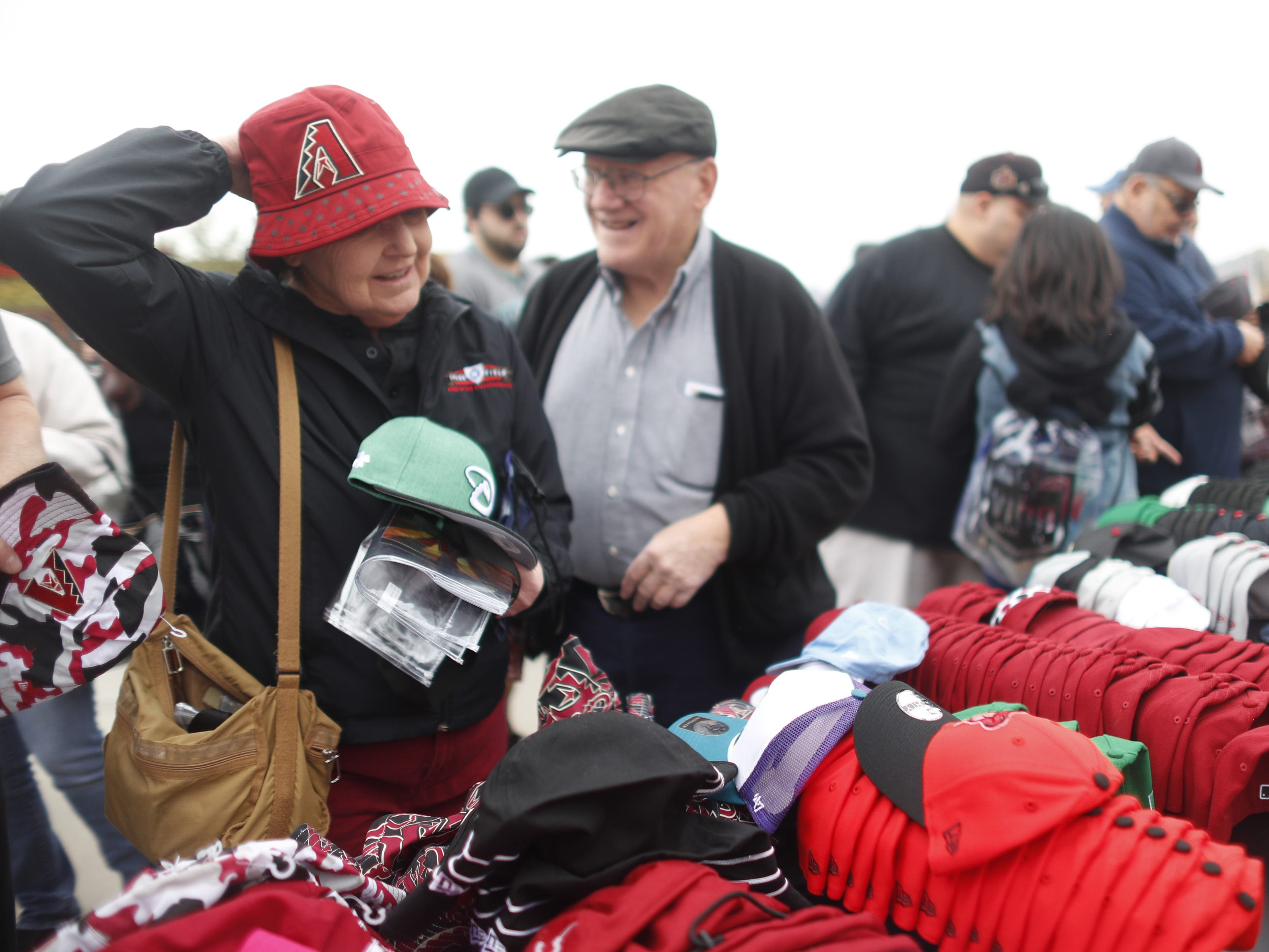 Kathy McCade (L) and her husband Joe McCade try on Diamondback hats that are on sale during the Diamondbacks Fan Fest at Salt River at Talking Sticks on February 9, 2019.