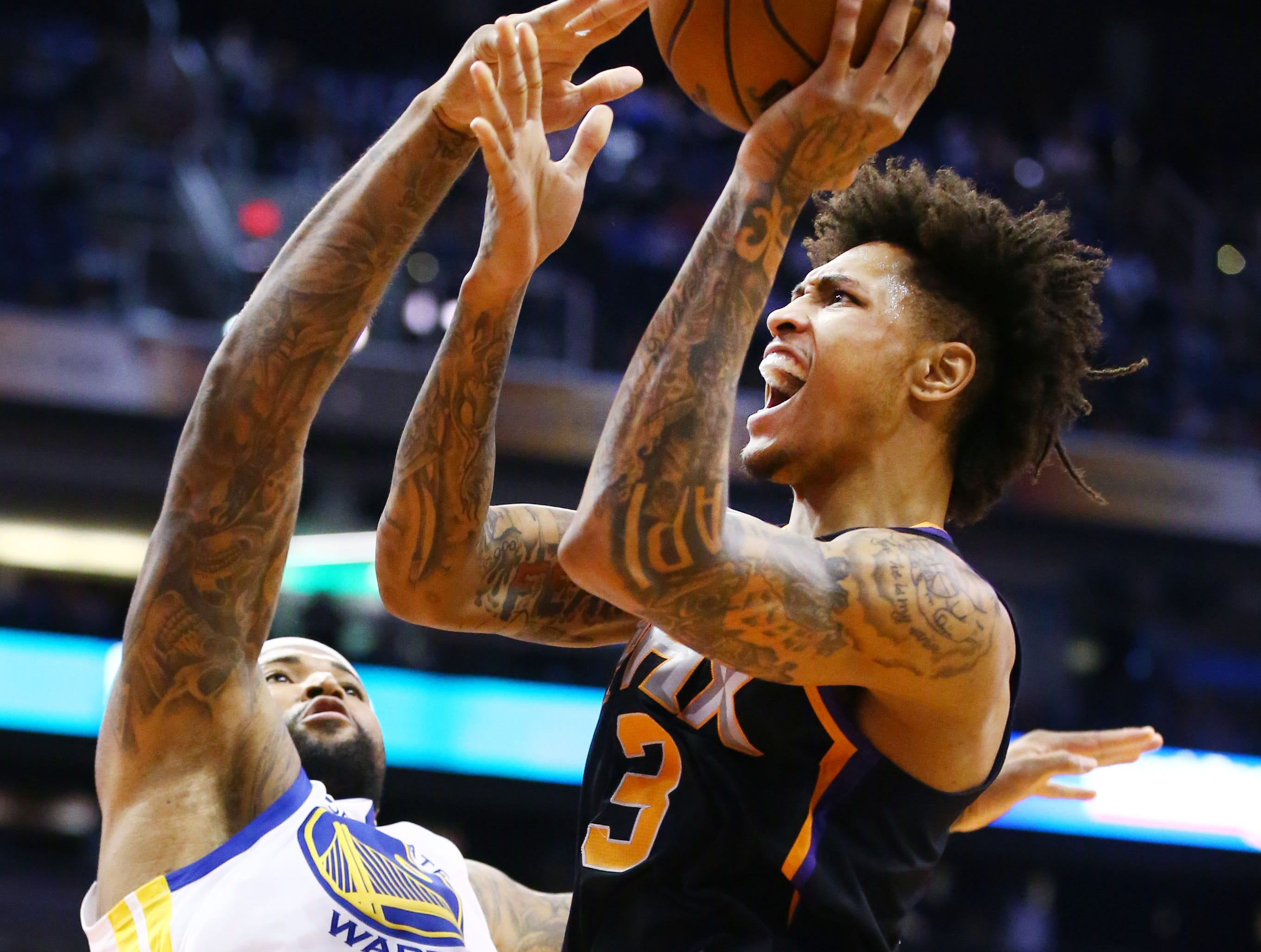 Phoenix Suns forward Kelly Oubre Jr. takes a shot against Golden State Warriors center DeMarcus Cousins in the first half on Feb. 8 at Talking Stick Resort Arena.
