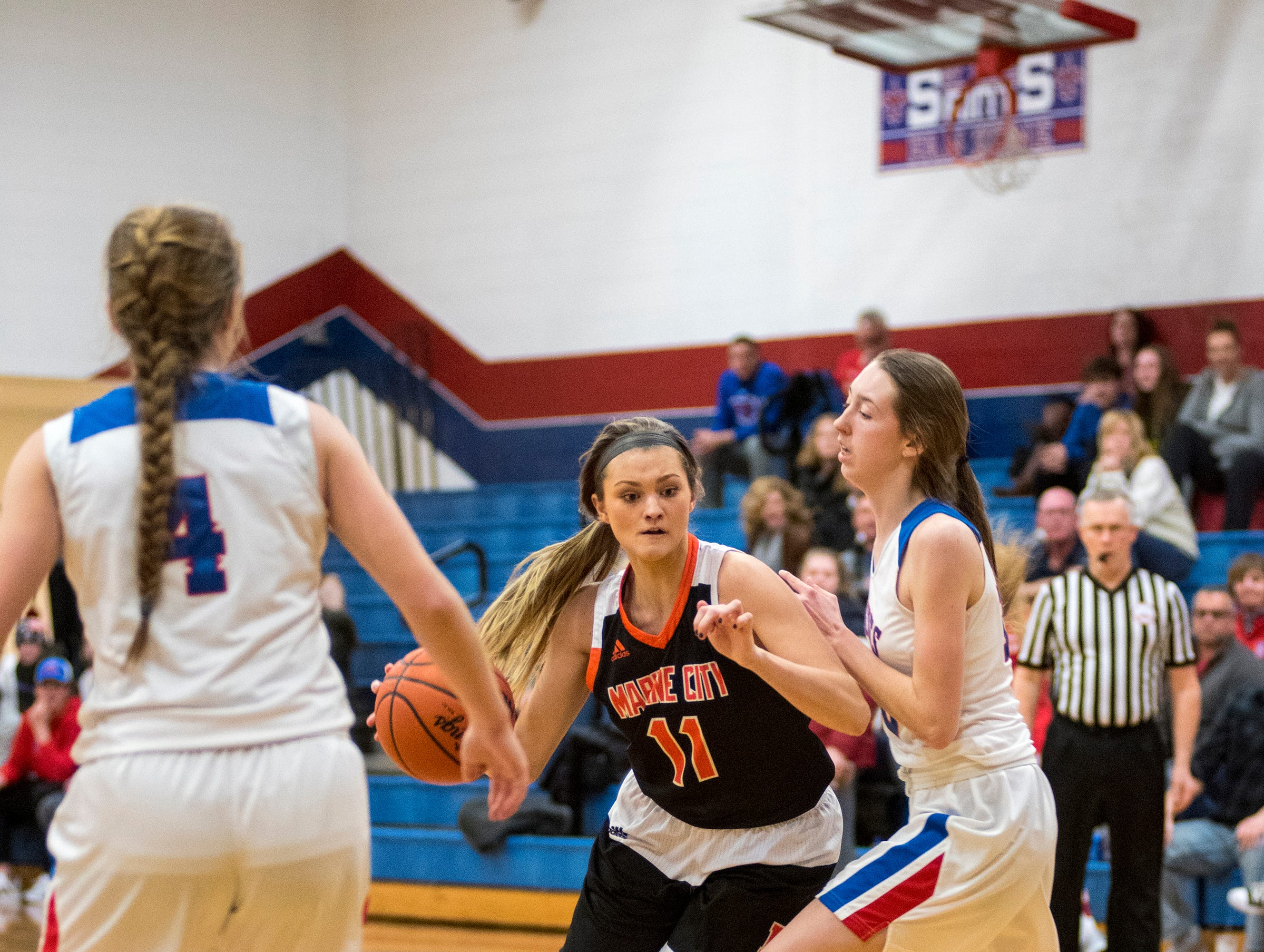Marine City High School's Kennedy Osterland (11) dribbles the basketball around St. Clair's Christina Bohm during their game Friday, Feb. 8, 2019 at St. Clair High School.