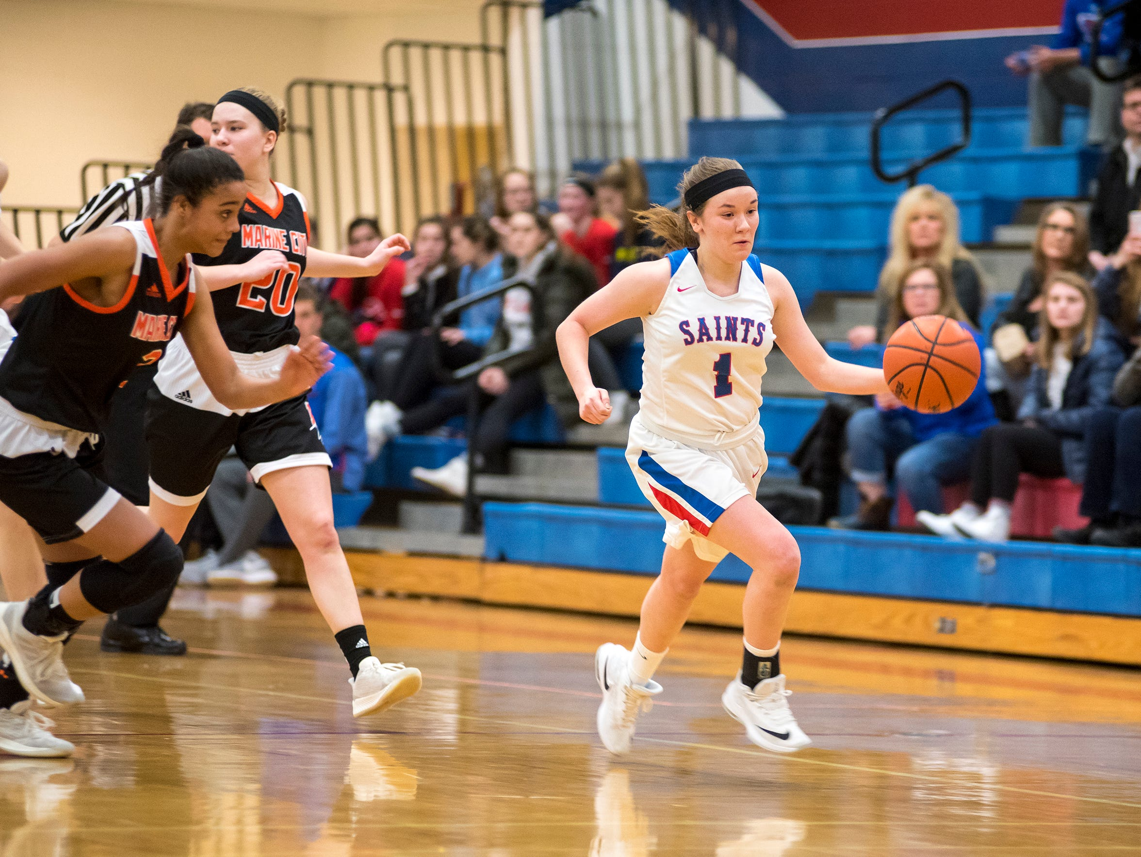 Players from Marine City High School chase St. Clair's Julianna Cataldo (1) as she runs with the basketball during their game Friday, Feb. 8, 2019 at St. Clair High School.