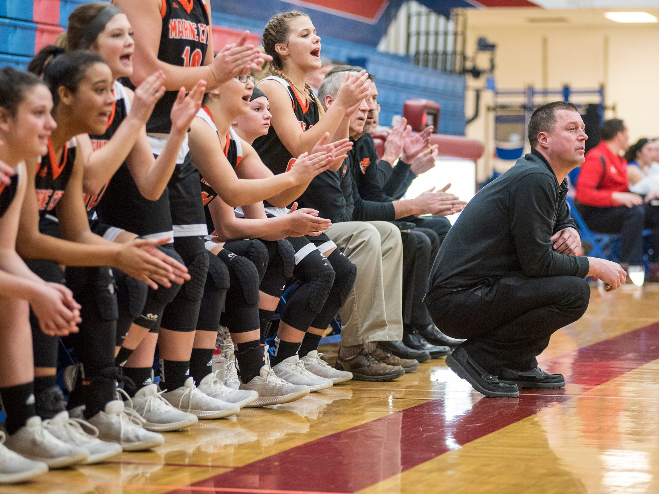 Marine City High School basketball coach Jeff Austin watches from the bench while the team cheers on a point behind him during their game against St. Clair Friday, Feb. 8, 2019 at St. Clair High School.