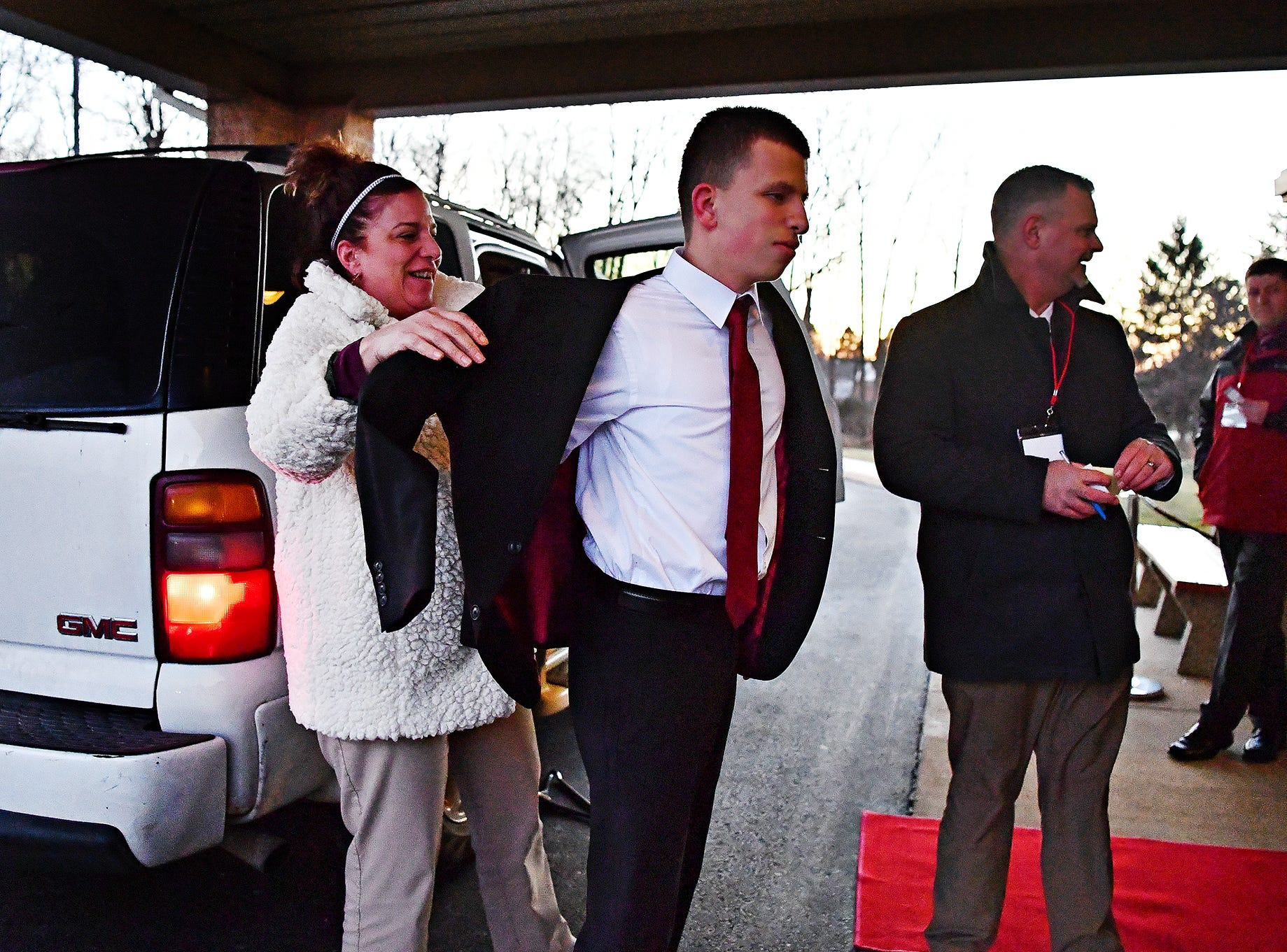 From left, Natalie D'Antoni, helps her son Frank D'Antoni, 18, with his suit coat as she drops him off for A Night to Shine, a Tim Tebow Foundation sponsored prom for people with special needs, at Friendship Community Church in Dover Friday, Feb. 8, 2019. Frank attends Lennard-Dale High School. Dawn J. Sagert photo