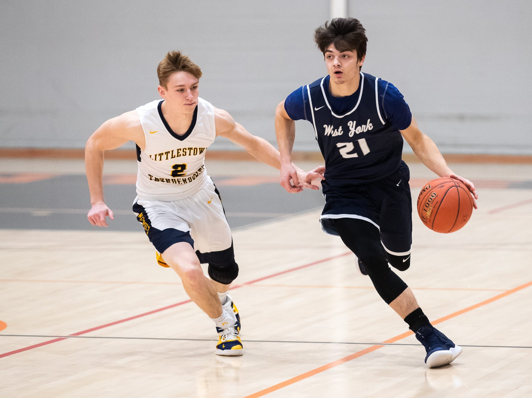 West York's Jared Shearer (21) drives down the court chased by Littlestown's Jakob Lane (2) during the first half of the YAIAA boys' basketball quarterfinals between Littlestown and West York, Saturday, Feb. 9, 2019, at Central York High School. West York led Littlestown 33-31 at the half.