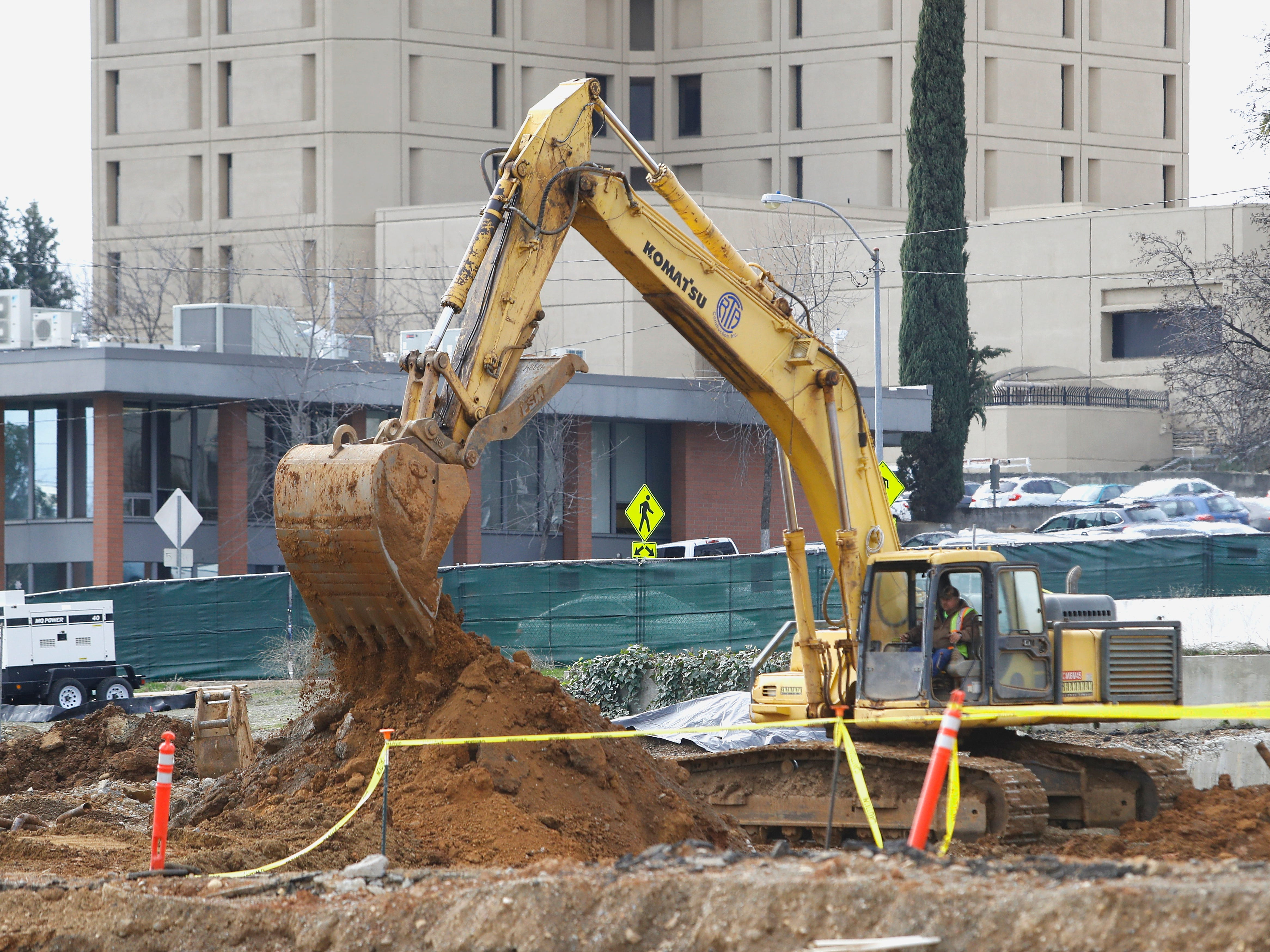 An excavator digs up dirt Friday at the site of the new Shasta County Courthouse on the same day dignitaries held a groundbreaking across the street.
