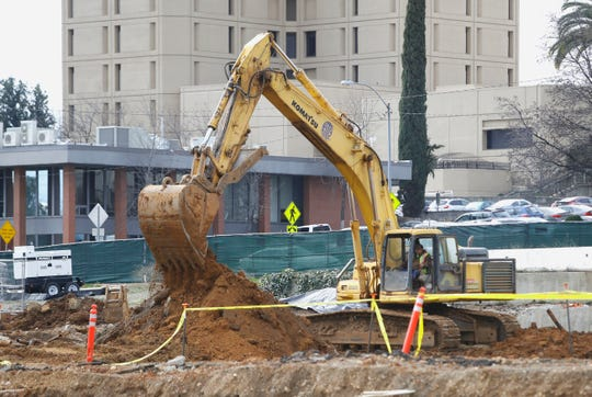 An excavator digs up dirt in February 2019 at the site of the new Shasta County Courthouse on the same day dignitaries held a groundbreaking across the street.